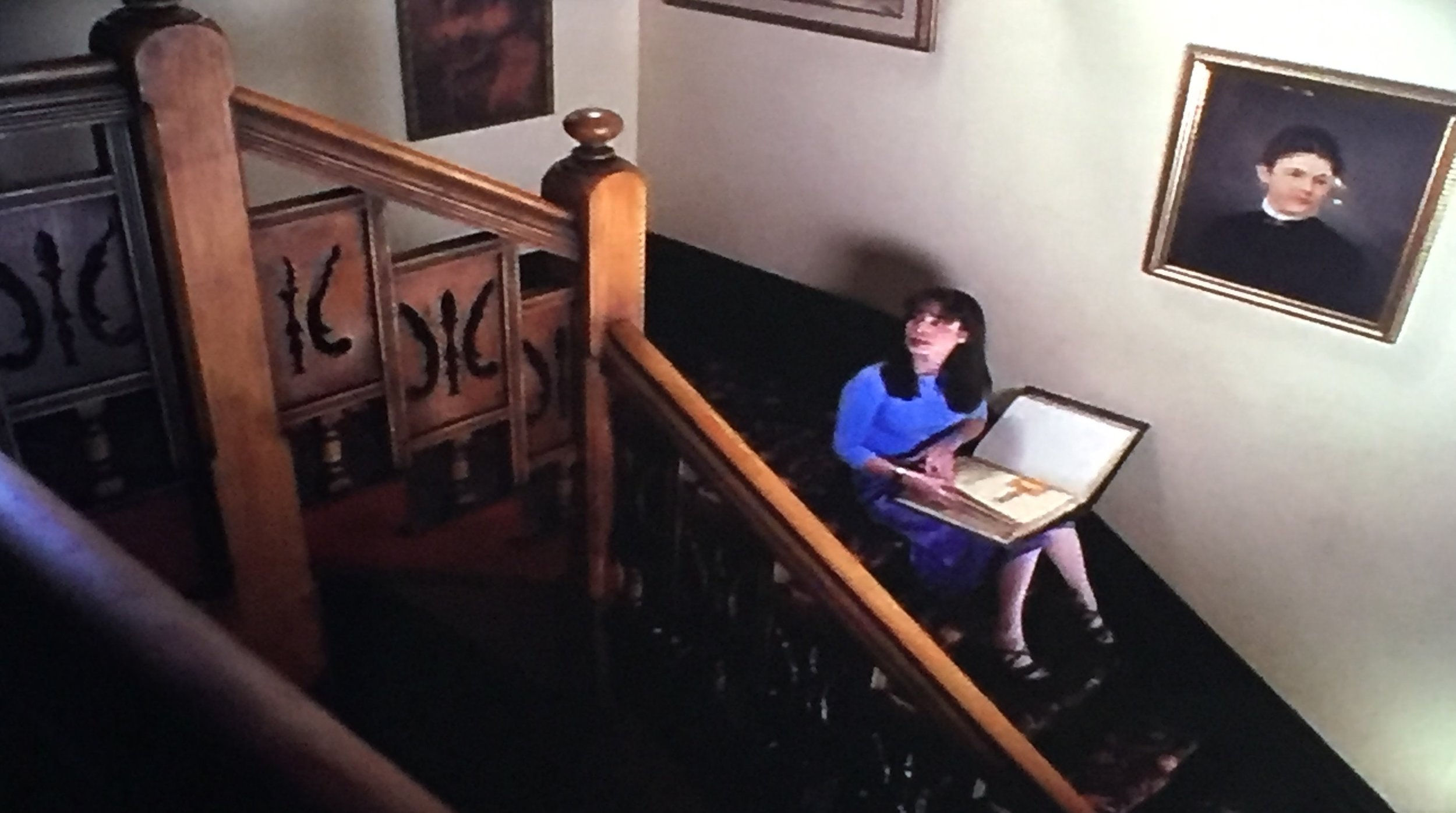 Piper sits on the stairs, reading the Book of Shadows...
