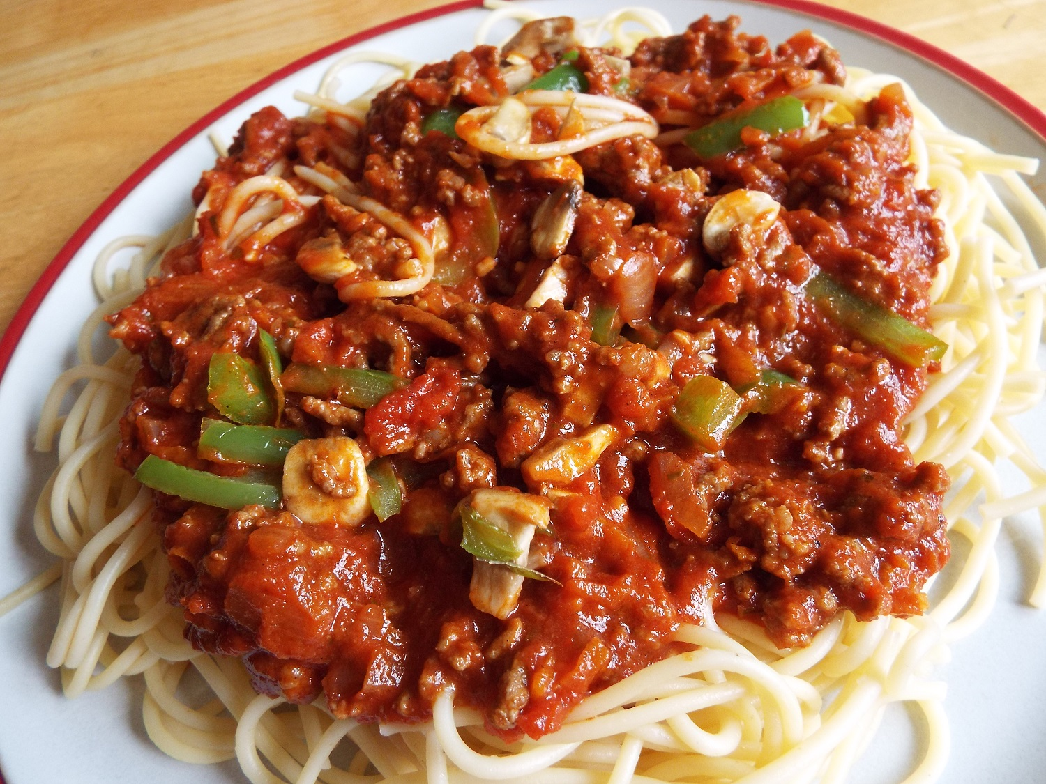 Spaghetti Bolognese - A dig classic - cook a big pot of spaghetti or pasta; and in another big pot fry chopped onion, and add minced beef or turkey, or soya or lentils. Add mixed herbs, garlic, chopped vegetables and tinned tomatoes.This plate of food uses beef mince, and green peppers and mushrooms. You can also use carrots, celery, courgettes and lentils. Seasoning can include a dash of Worcestershire sauce for that garum experience.