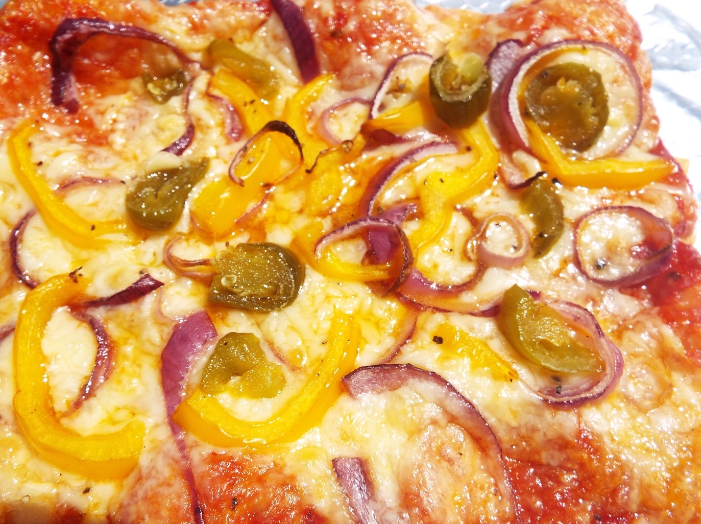 Pizza Tray Bake - Heat oven. Roll out pizza dough (you can use pre-made or pizza dough mix), add the pizza tomato topping.Add grated cheese and all the toppings - this one has onion, yellow peppers and green jalapenos. Add seasoning.Bake in a hot oven for about 30 minutes.