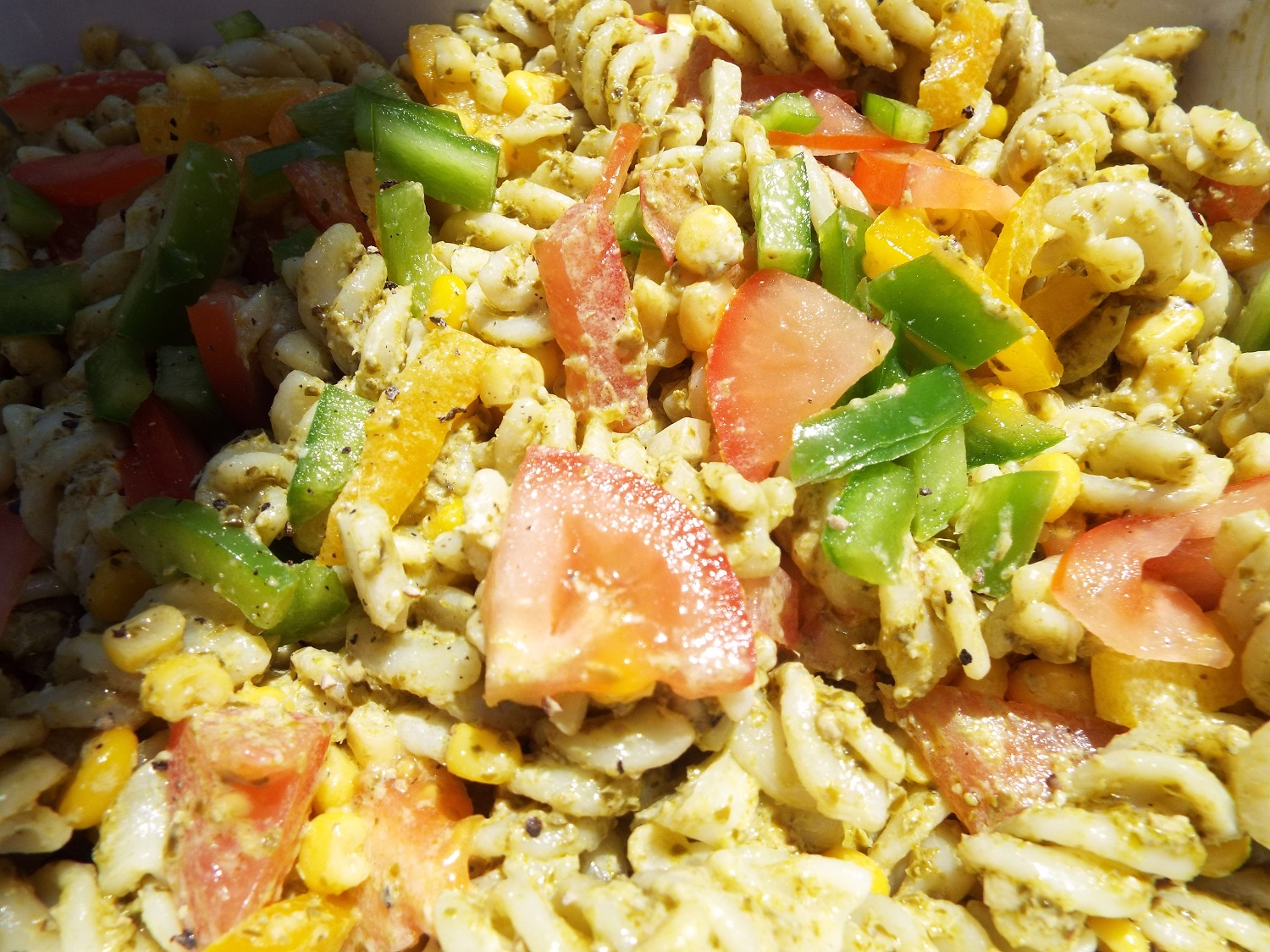 Pasta Salad Bowl - Cook pasta shapes, add a dressing like mayo or pesto, and seasoning.Add chopped salad vegetables - this bowl has tomatoes, onion, green peppers, yellow peppers and sweetcorn.