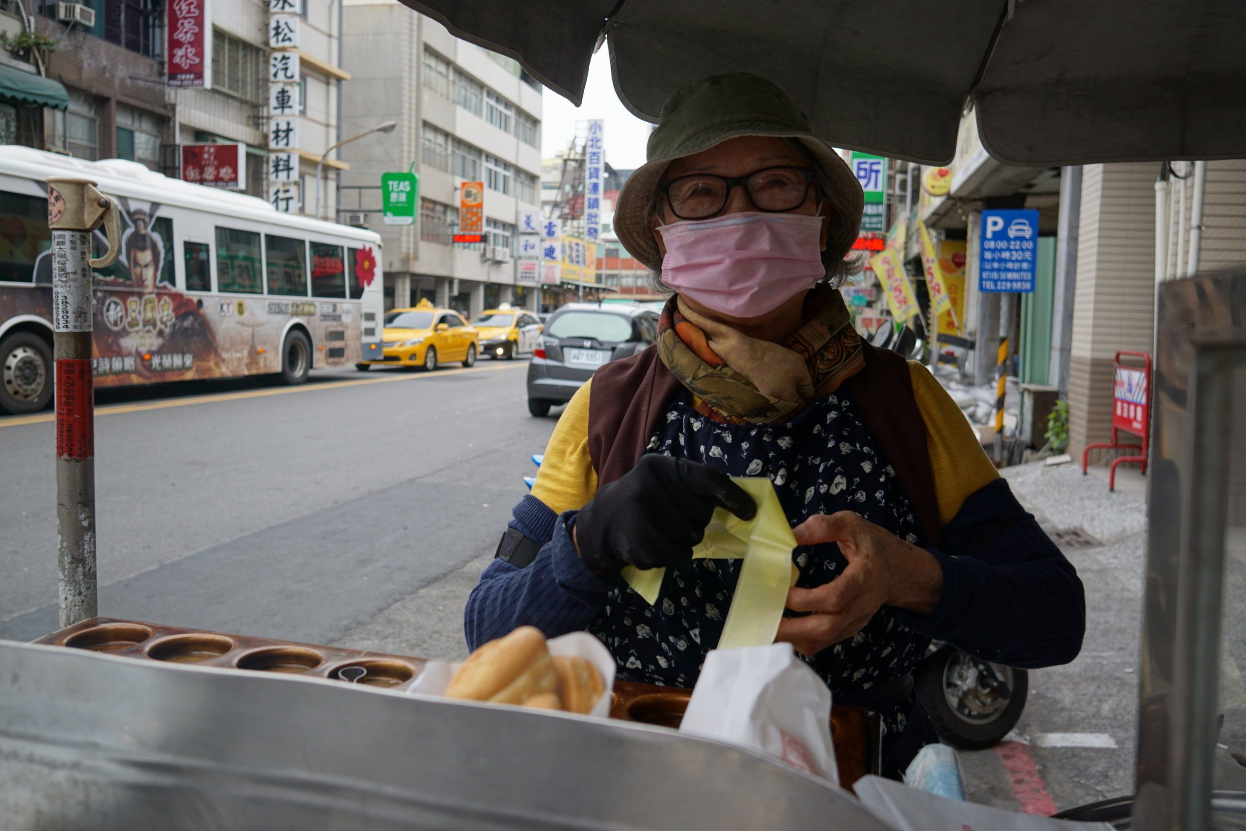 Air pollution blights kaohsiung, the port city where it is home to many huge and polluting industries, A lady dons a mask as she bakes taiwanese pancakes