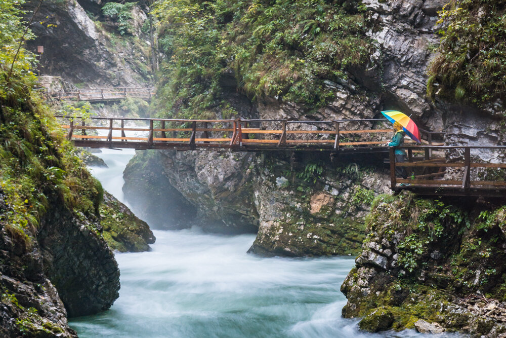 At the end of the gorge in Slovenia, a suspension bridge hangs above the 40-foot tall Sum Waterfall
