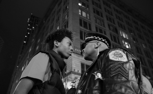 Den 16-årige aktivist Lamon Reccord nedstirrer en politibetjent under en protest i Chicago d. 25. nov. 2015 mod en hvid betjents fatale nedskydning af 17-årige Laquan McDonald året før. Foto: John J. Kim / Chicago Tribune