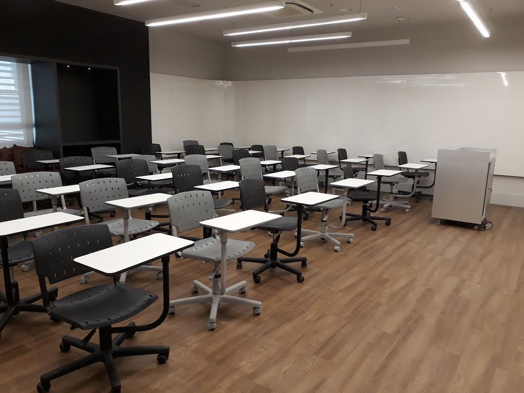 Quadro branco 270º, projetor, cadeiras articuláveis e lounge ao fundo