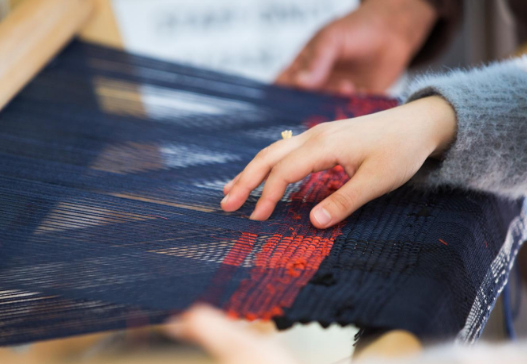 An image of a woman weaving in Thistle Farms'  new social enterprise