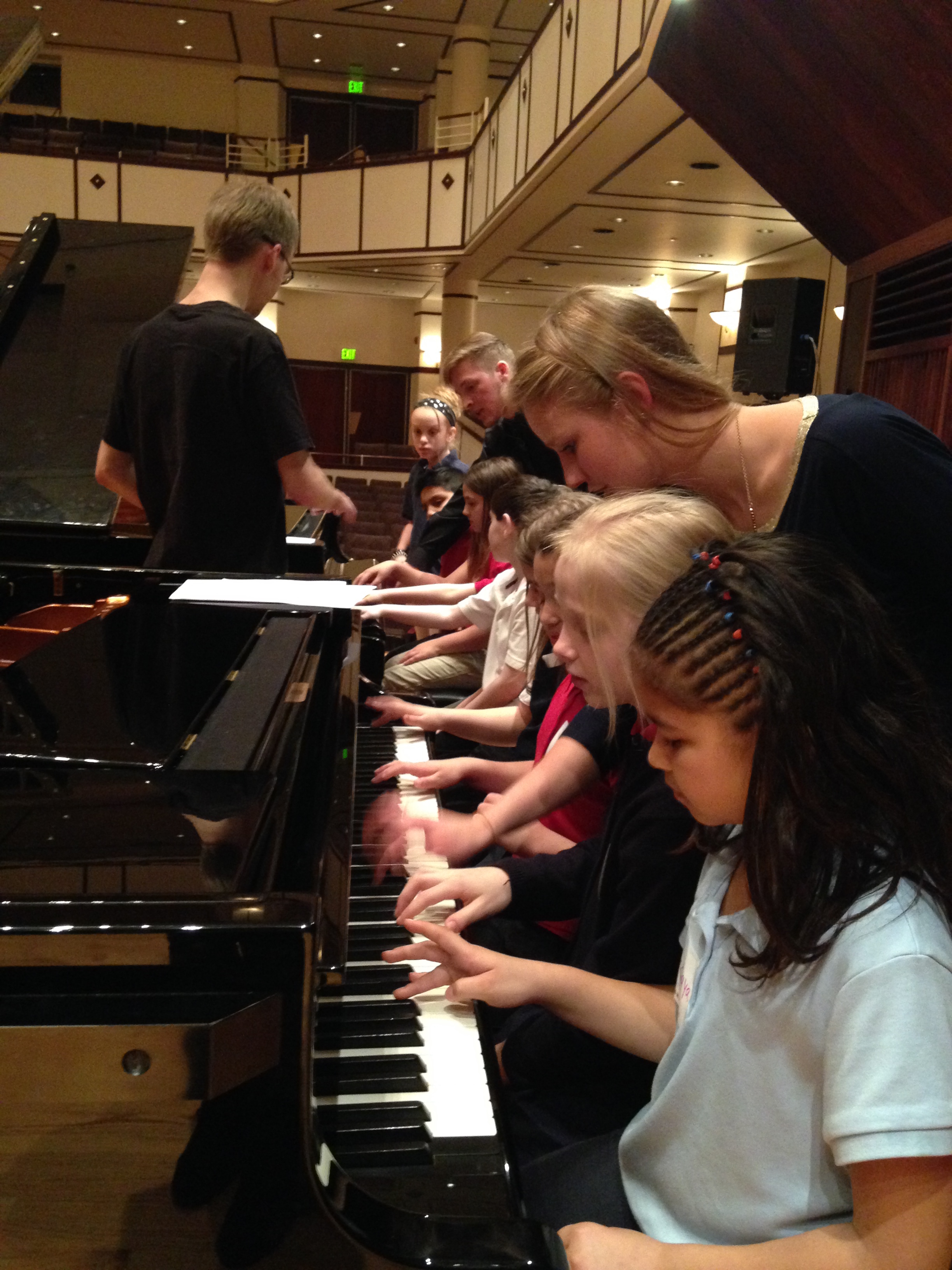 IPS #34 third graders trying out pianos with UIndy music education major students.
