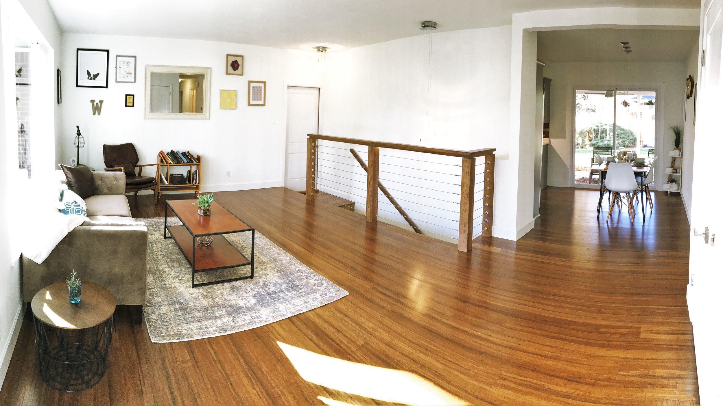 A custom hickory railing by Pin and Scroll maintains the feeling of openness in the living room. Old growth, stranded bamboo was chosen for the floor because of its hardness and environmental sustainability. The front  door was reclaimed and carefully restored.