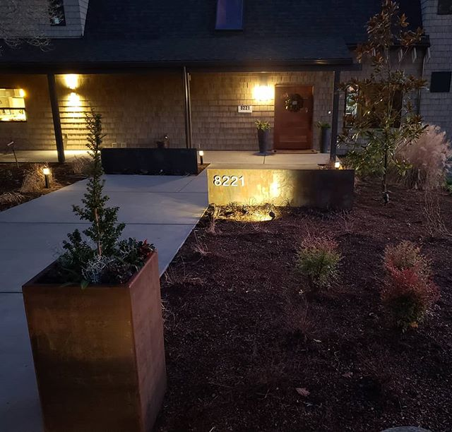 """A night shot of a recent install.  The work included a pair of 30"""" tall column planters,  address numbers, and steel walls.  Design by @designsbydeleuw  #landscapedesign #steel #planters #cortensteel #gardendesign #cleanlines"""