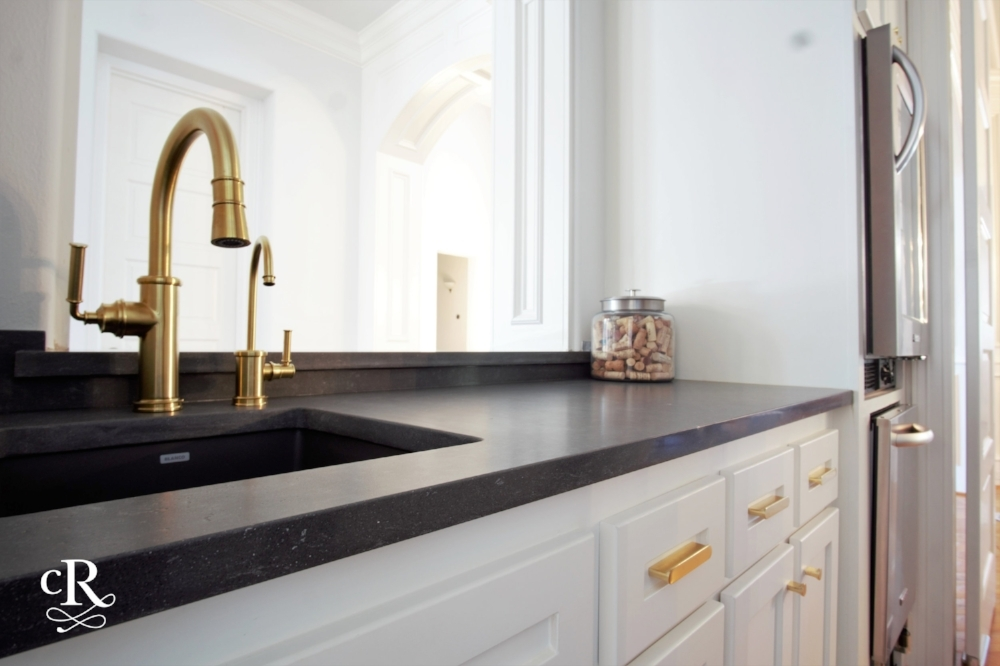 The fresh, new wet bar with dark charcoal quartz and brass plumbing fixtures.