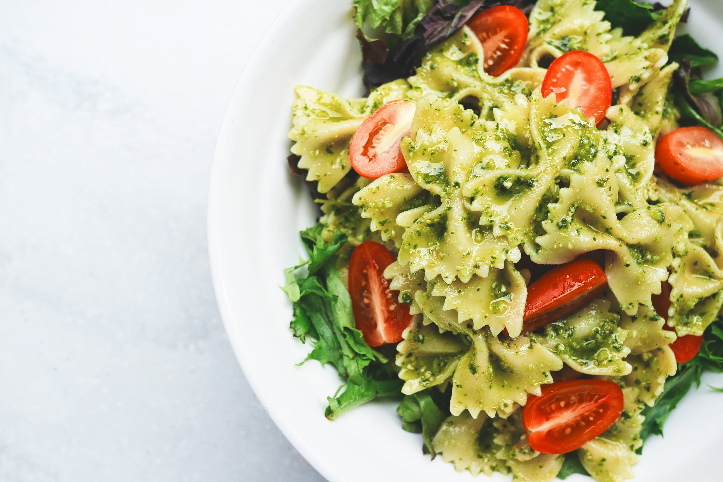 Gluten free bowtie pasta with cherry tomatoes and pesto on a bed of fresh arugula
