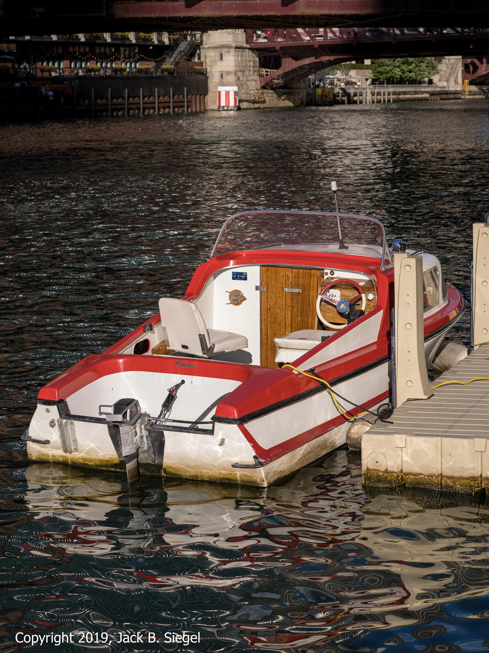 A Classic Motorboat from the Sixties is Docked at the River Walk, with the Sun Still Casting Its Warm Light