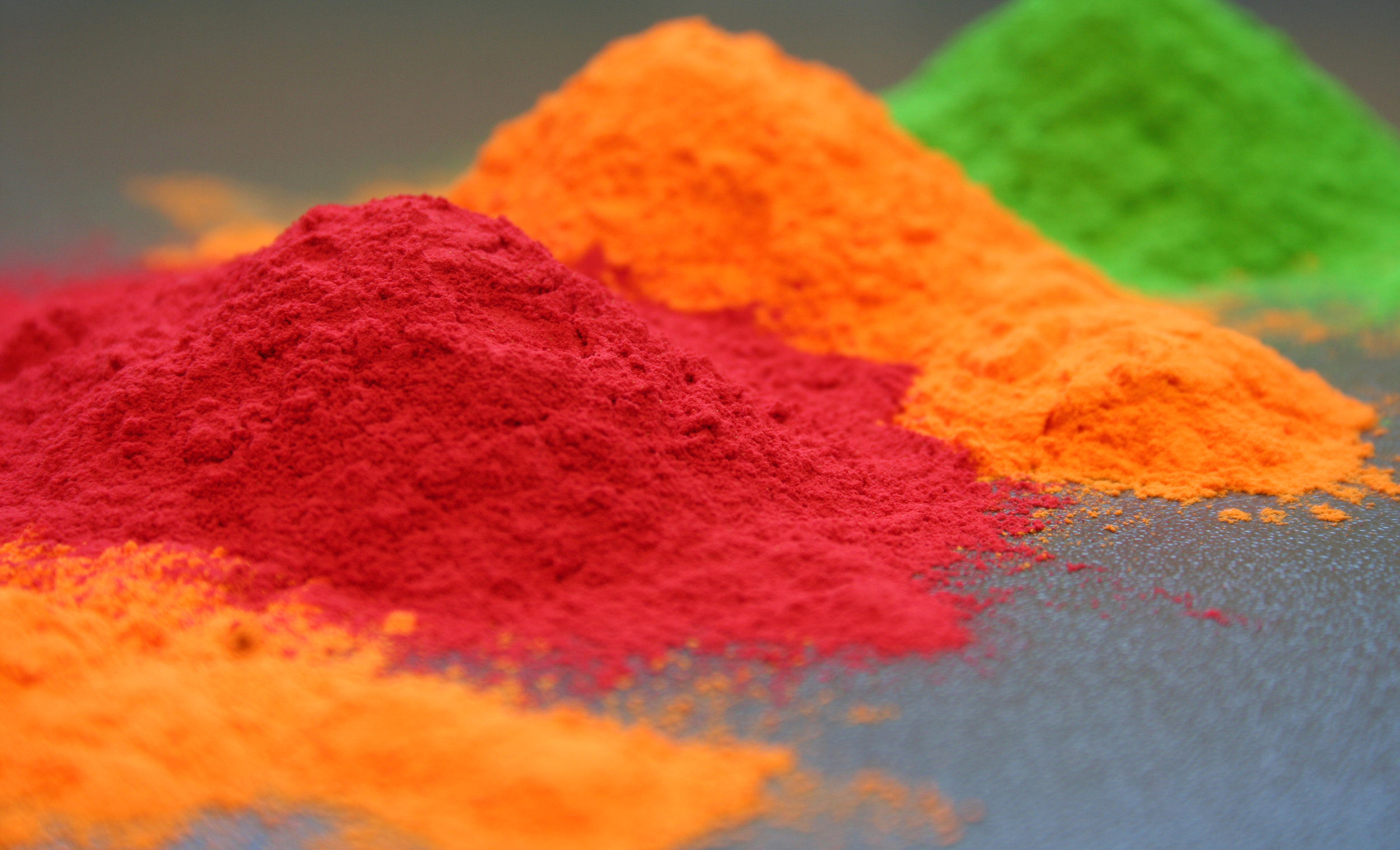 Powder for powder coating metal parts in red, orange & green.