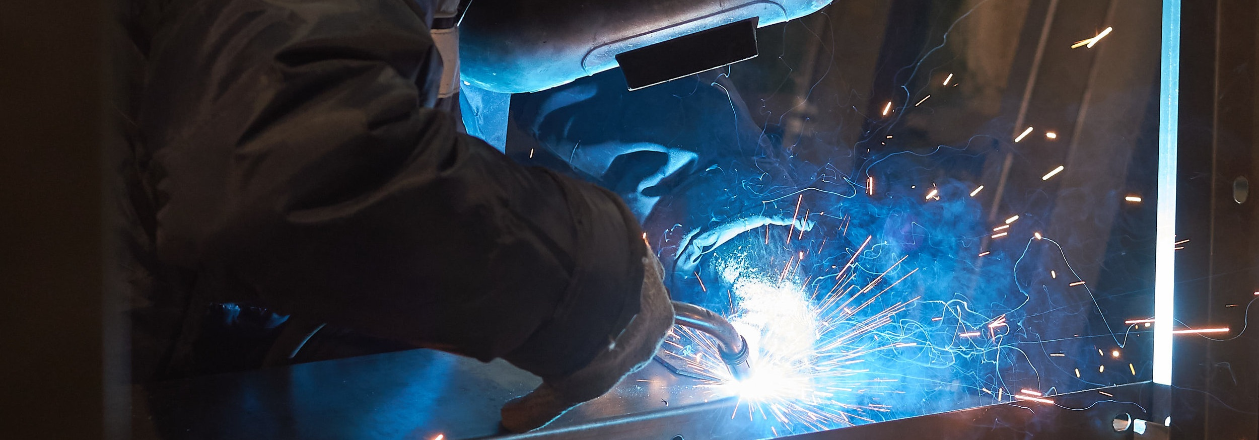 Welder joining pieces of metal during the part fabrication process.