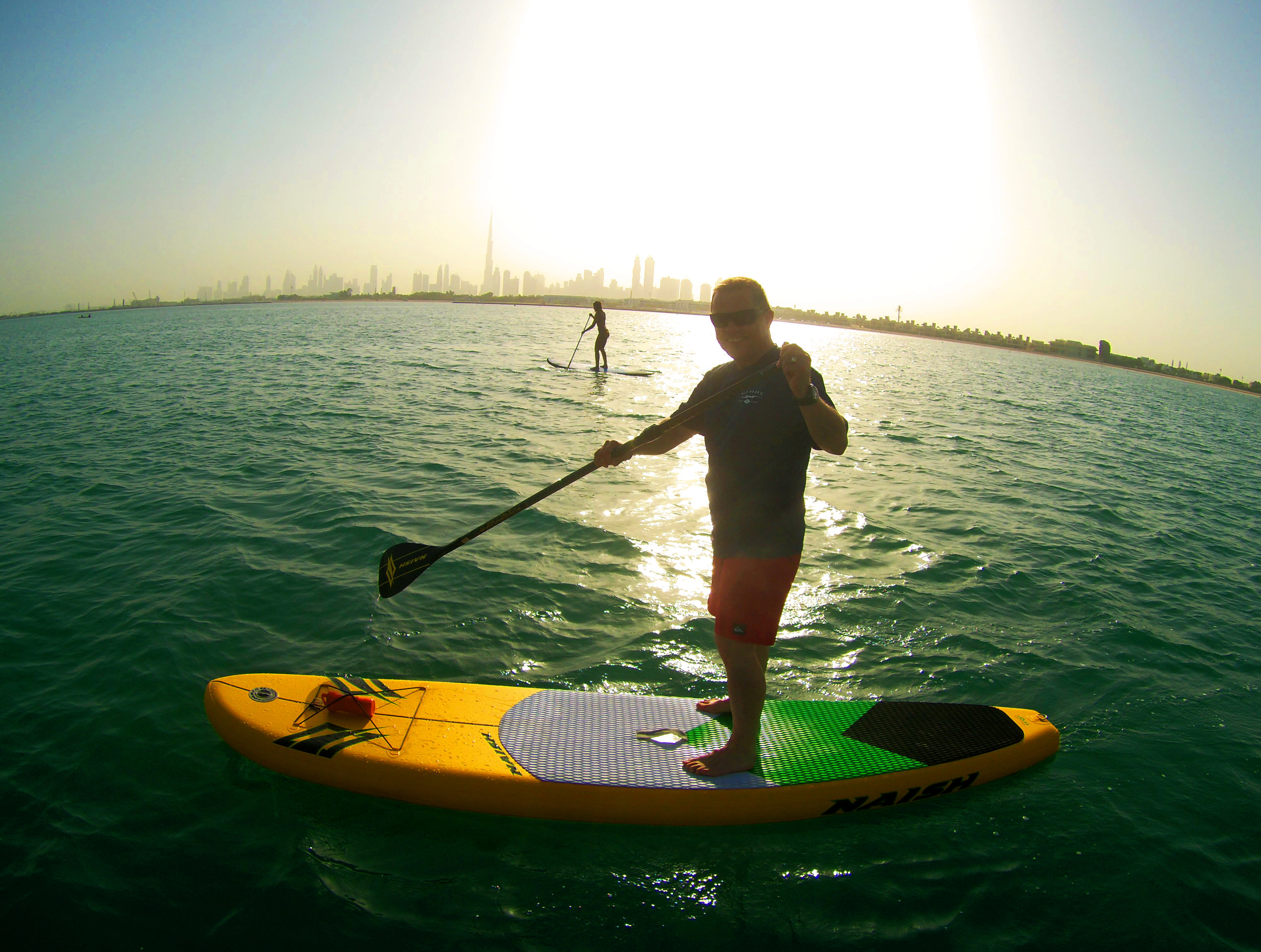 Toby on the SUP with girl in background.jpg