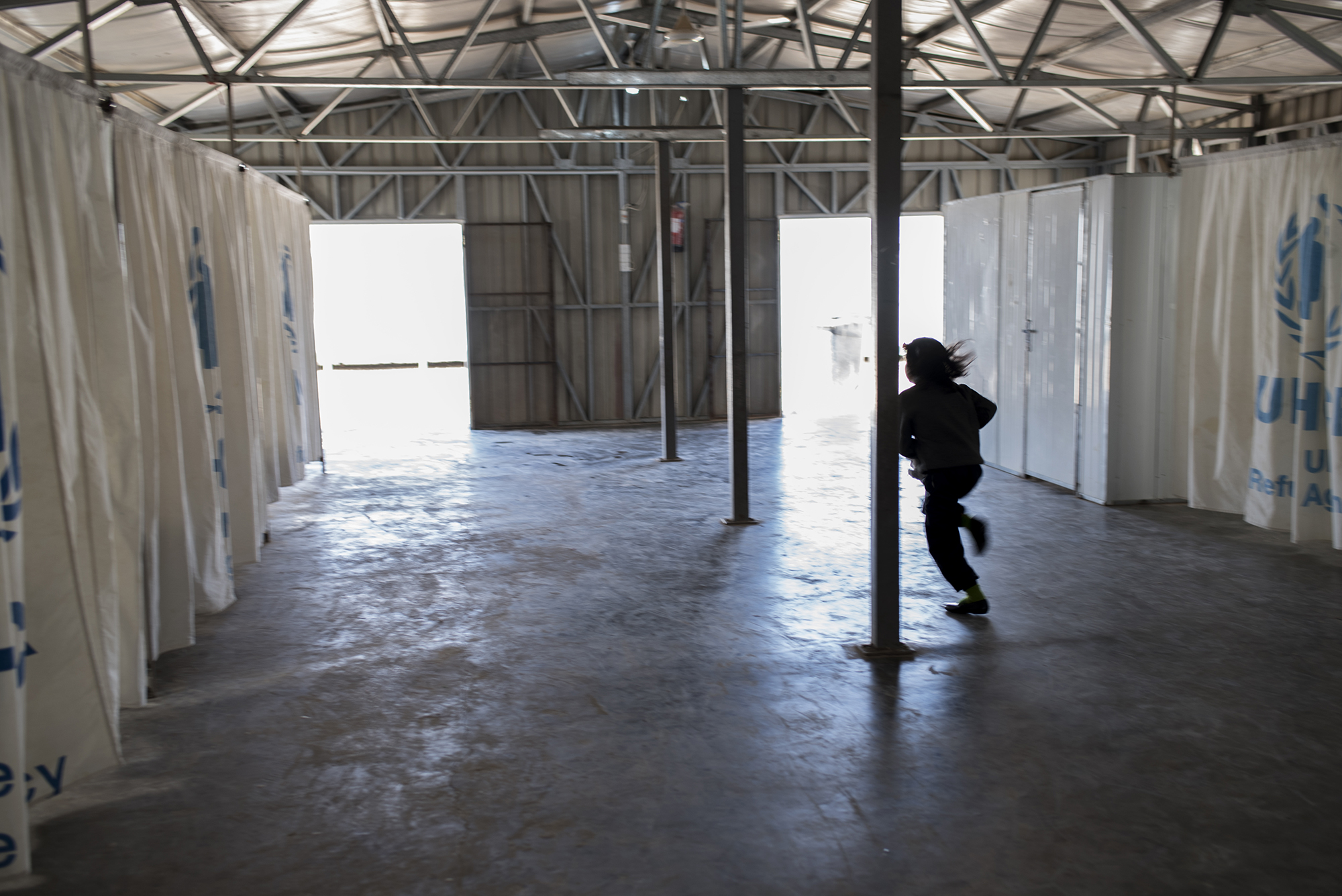 A Syrian child runs through a temporary shelter inside Jordan's Zaatari refugee camp, where vulnerable families wait for assistance upon arriving in the camp. February 2016.