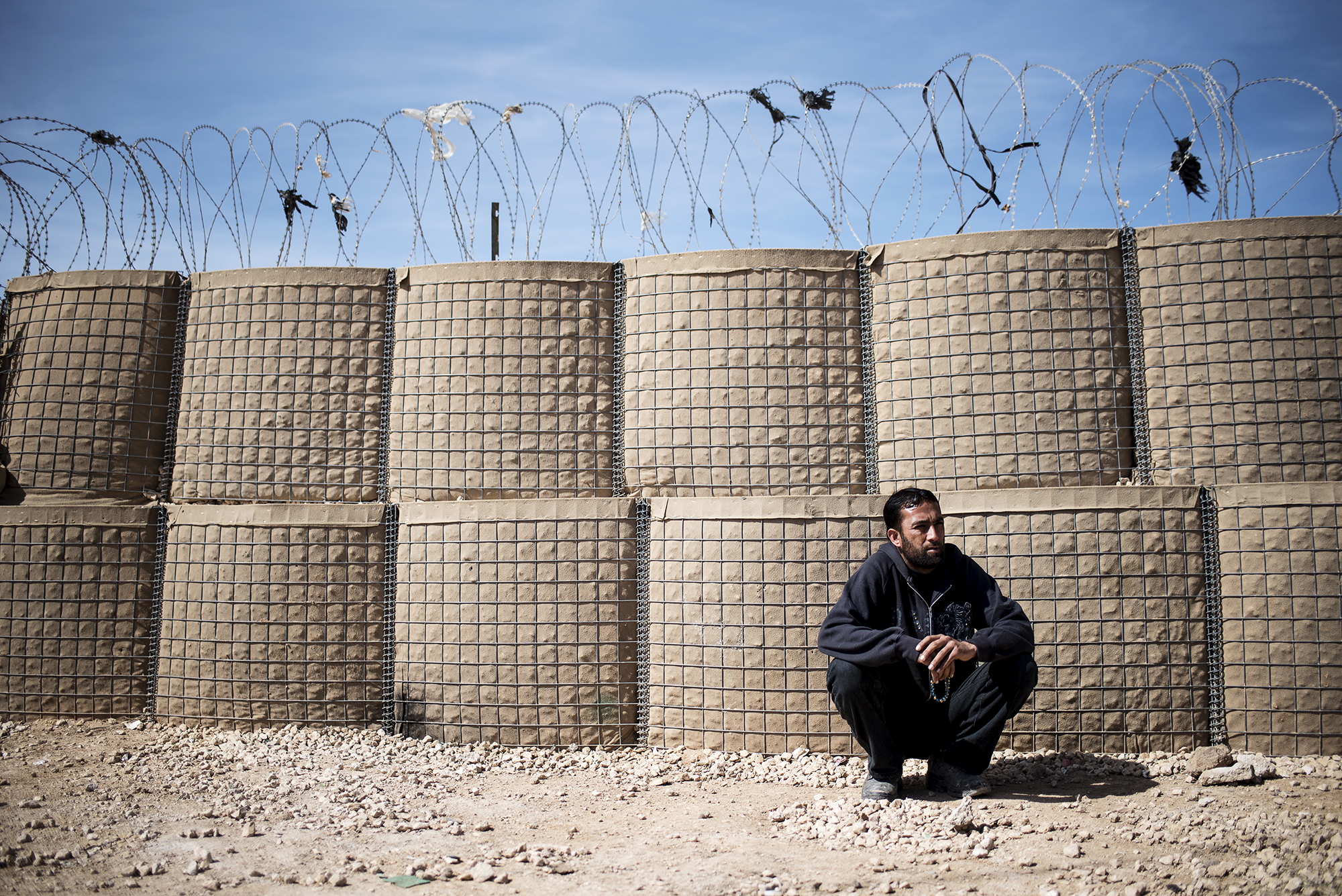 A man rests along a fence in Jordan's Zaatari refugee camp, some six miles from the country's northern city of Mafraq. February 2016.