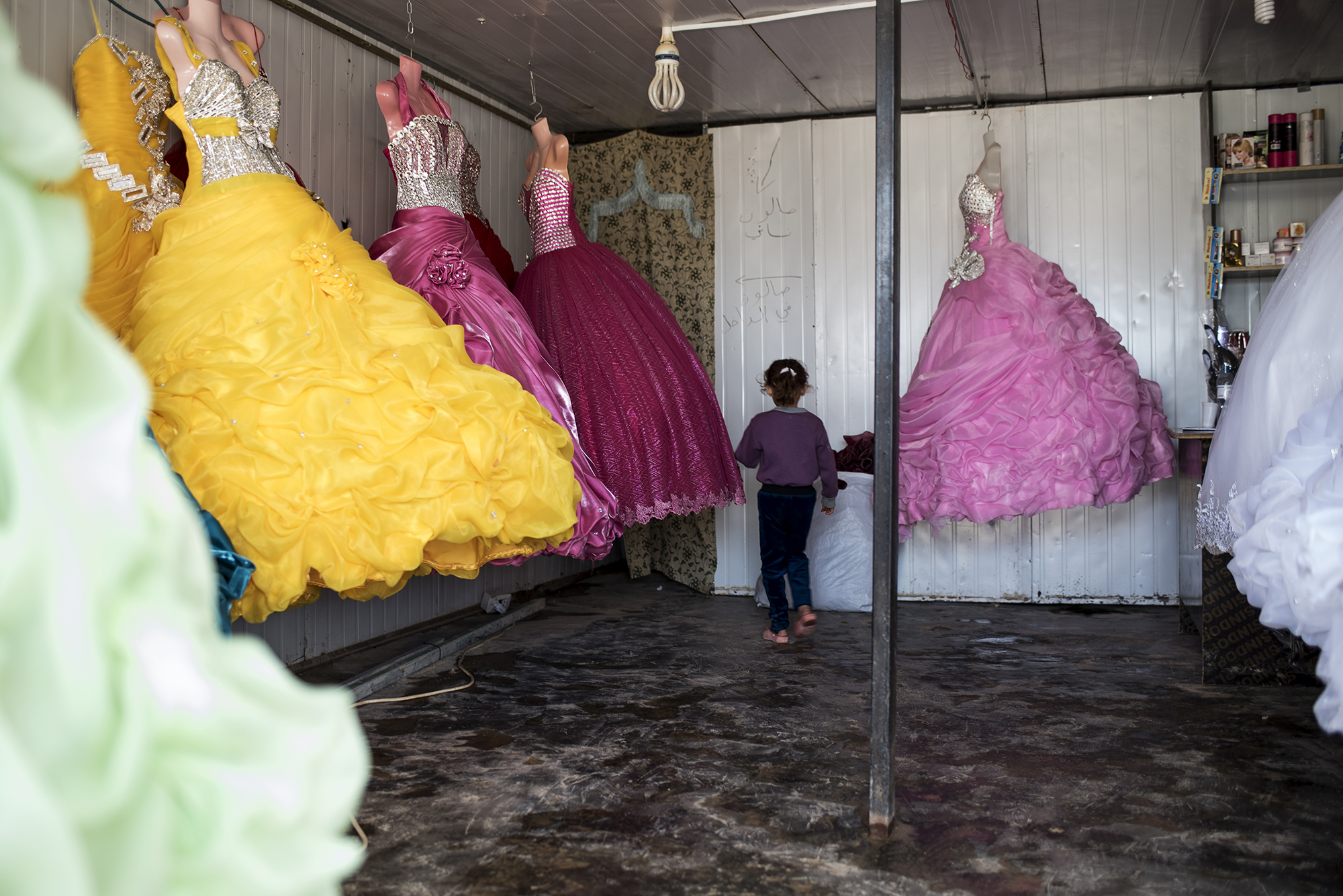A child walks through a wedding dress shop in the central market of Jordan's Zaatari refugee camp, October 2015.