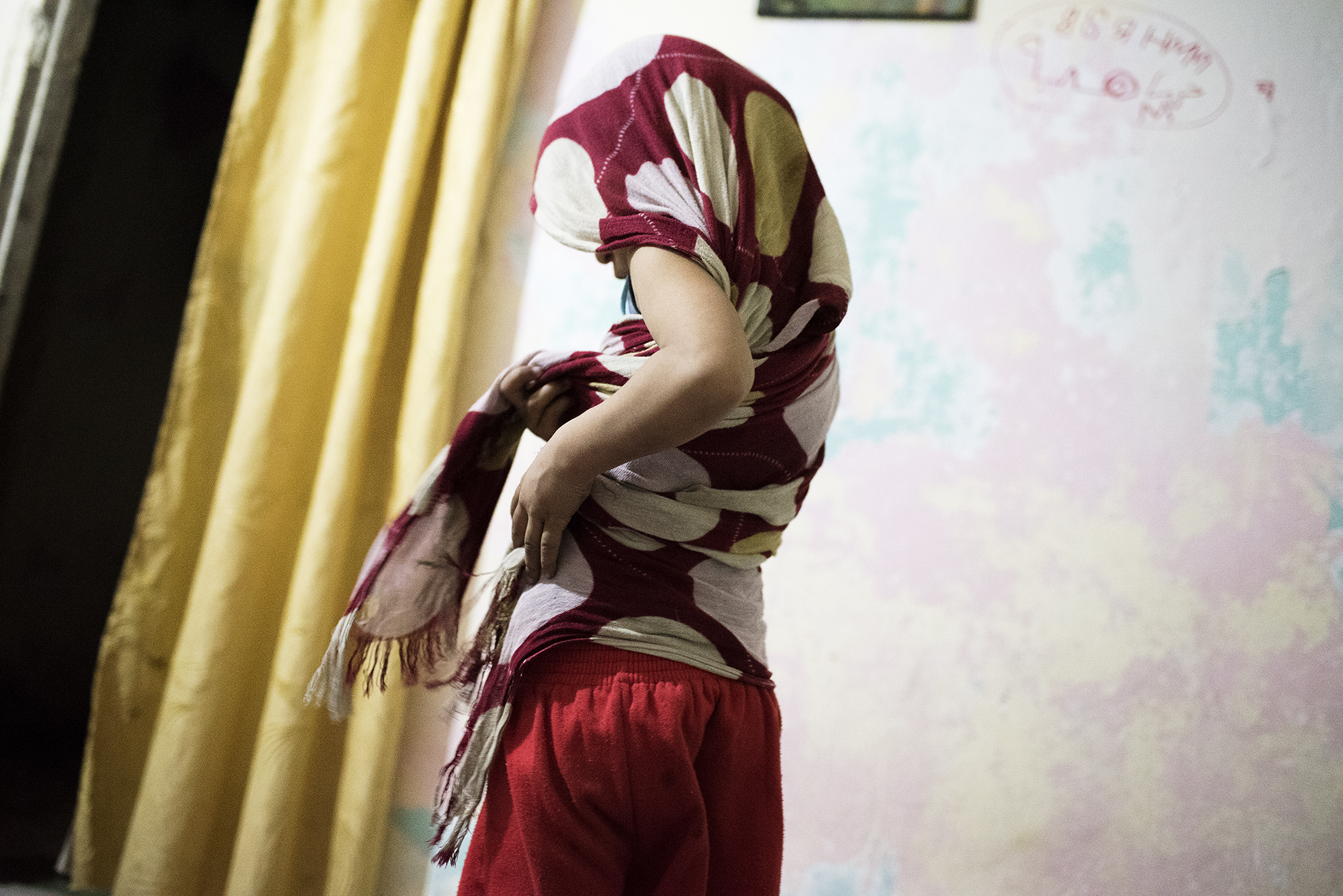 A girl from the western Syrian city of Hama adjusts a scarf in an apartment in the outskirts of Beirut, Lebanon, where she and her mother fled following violence in Hama in 2012.