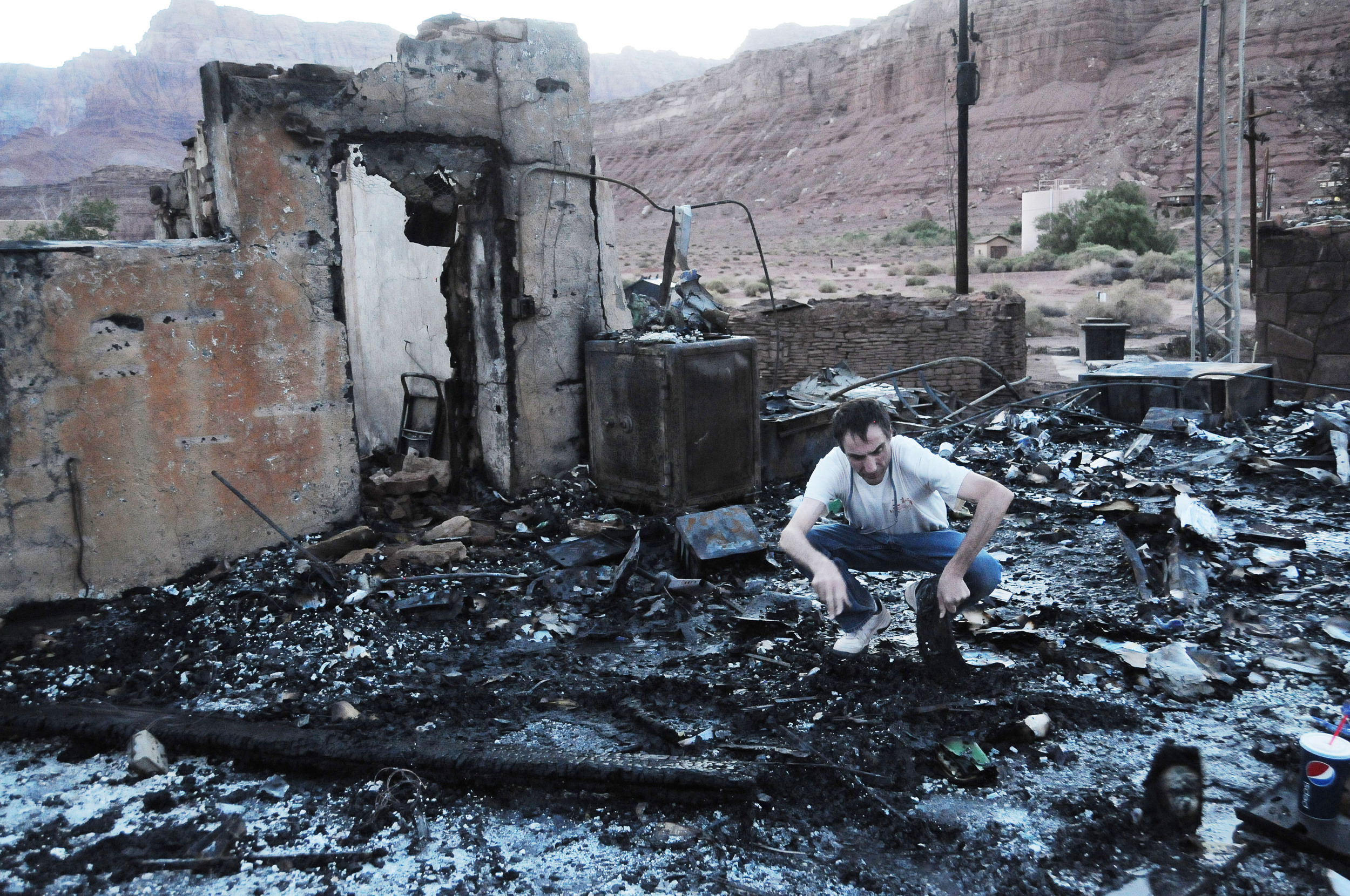 Marble Canyon Lodge manager Barry Adams searches for his office keys in the charred rubble of Arizona's Marble Canyon Lodge. Built in 1926, The lodge is located near the Grand Canyon's North Rim and is a historic pit stop for Grand Canyon and Colorado River tourism. The fire was a result of a gas leak in the lodge's kitchen around 1 a.m. and was unable to be quickly responded to due to the landmark's remote location on the Arizona Strip. June 2013.