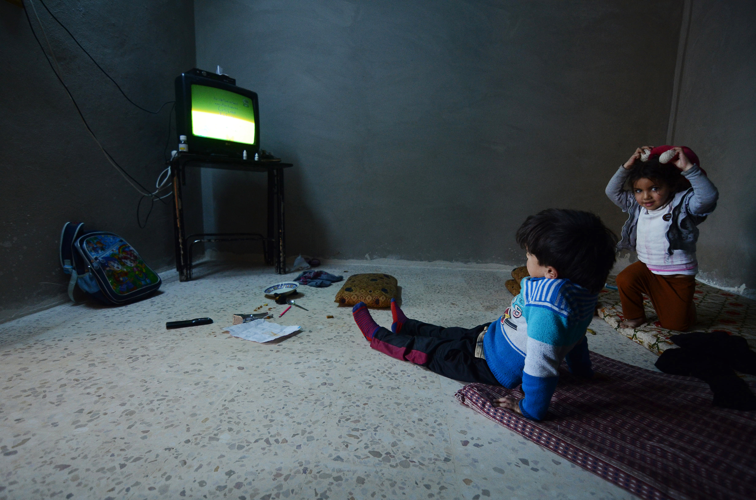 Syrian refugee children watch a TV program inside an empty room of their new home in Irbid, some 50 miles north of Jordan's capital Amman. March 2015.