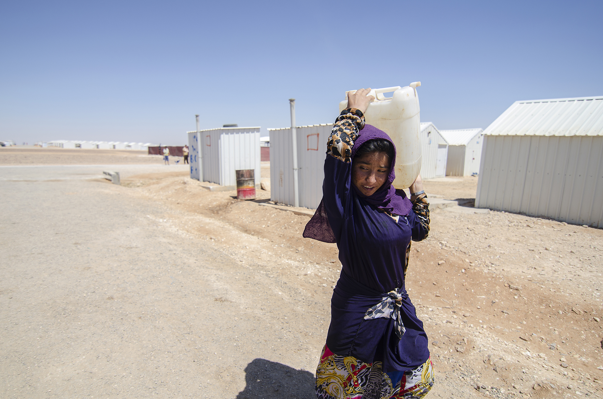 A refugee carries water back to her family's caravan in Jordan's Azraq Refugee Camp for Syrians, opened May 2014 in the country's eastern desert province and camp namesake, Azraq. Unlike Zaatari's chaotic, impromptu inception, Azraq's development was preplanned by the UNHCR as an humanitarian response to increasing numbers of refugees.  See more at Al Jazeera.  June 2015.