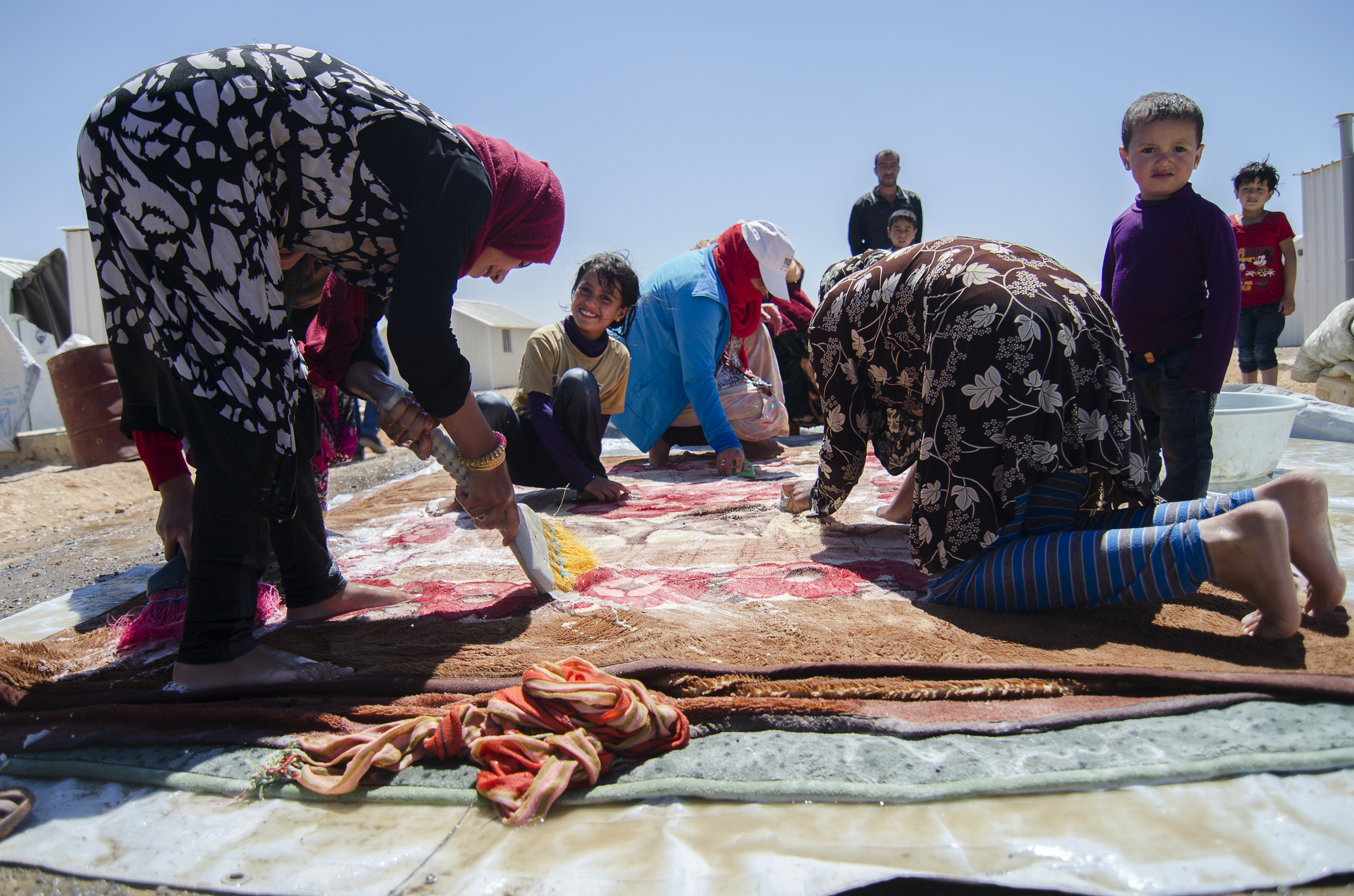 Azraq residents wash blankets outside their metal shelters. Residents say scalding summer temperatures, high food prices and the lack of electricity make the desert camp a harsh option to sustain. June 2014.