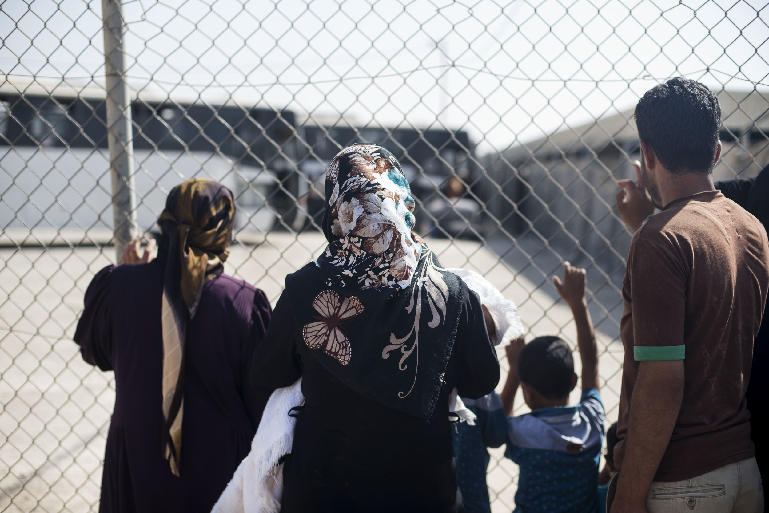 Zaatari camp residents watch as family members load onto buses headed out of the camp and back to Syria. October 2015.