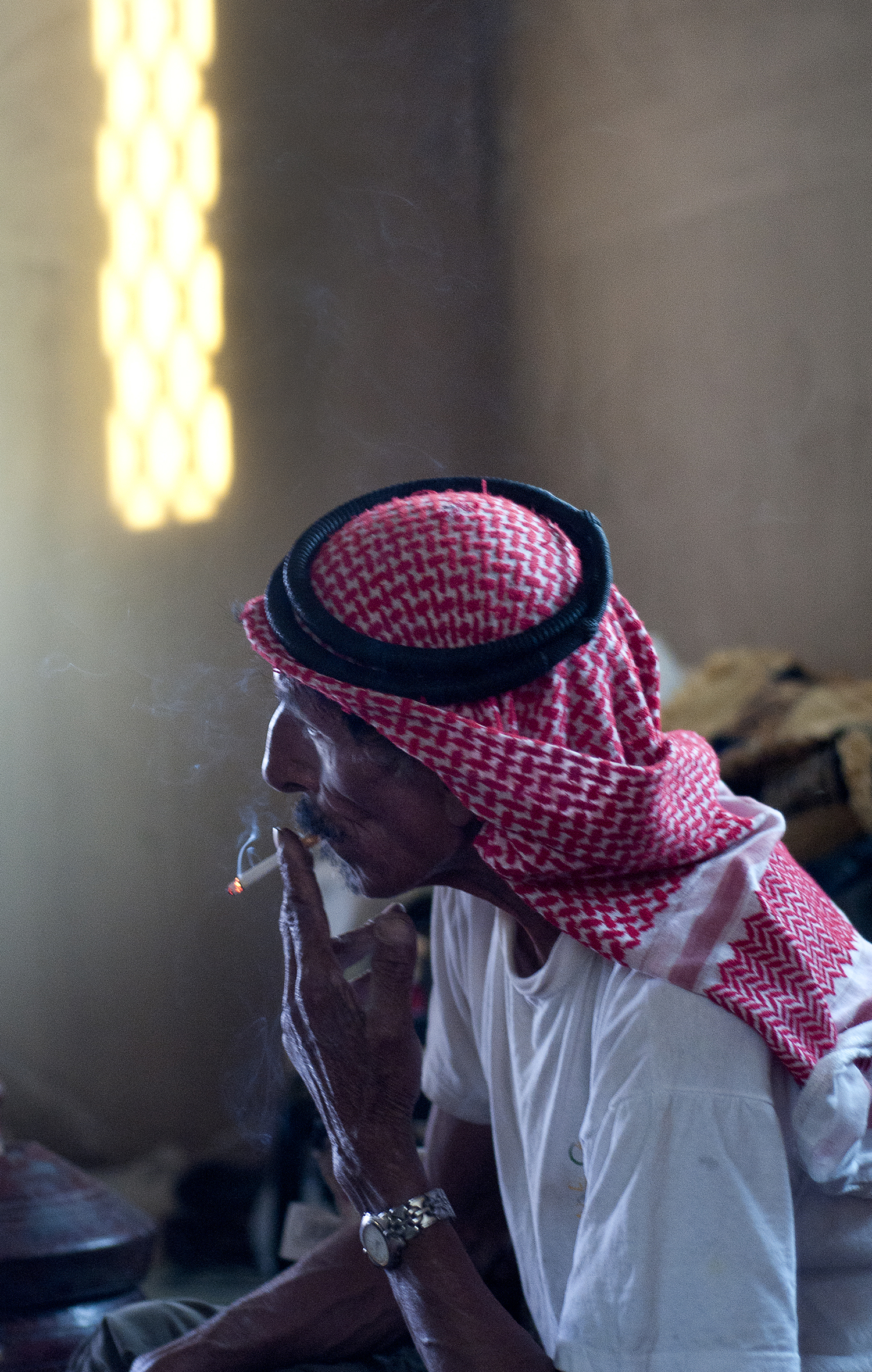 Bani Murra tribal elder Abu Hussain smokes a cigarette in his home in the outskirts of Amman. The tribe has broader roots in the Arabian Penninsula, where larger groups of Bani Murra began migrating in the early 1800s to settle throughout Jordan, Israel, Syria, Saudi Arabia and Egypt. July 2013.
