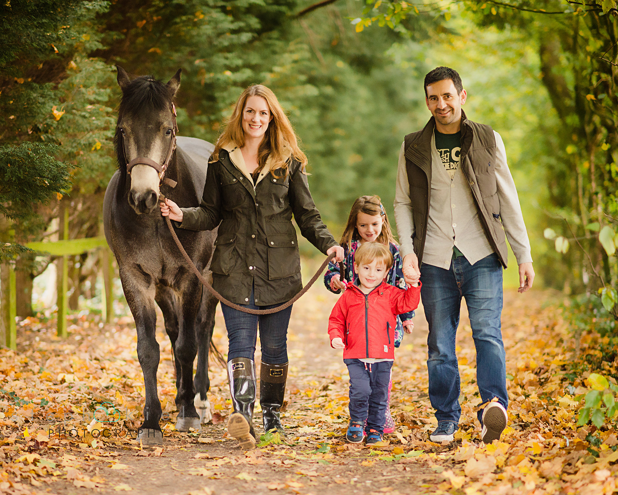 Family walking in the woods with their horse during a photo session in aylesbury buckinghamshire and thame oxfordshire