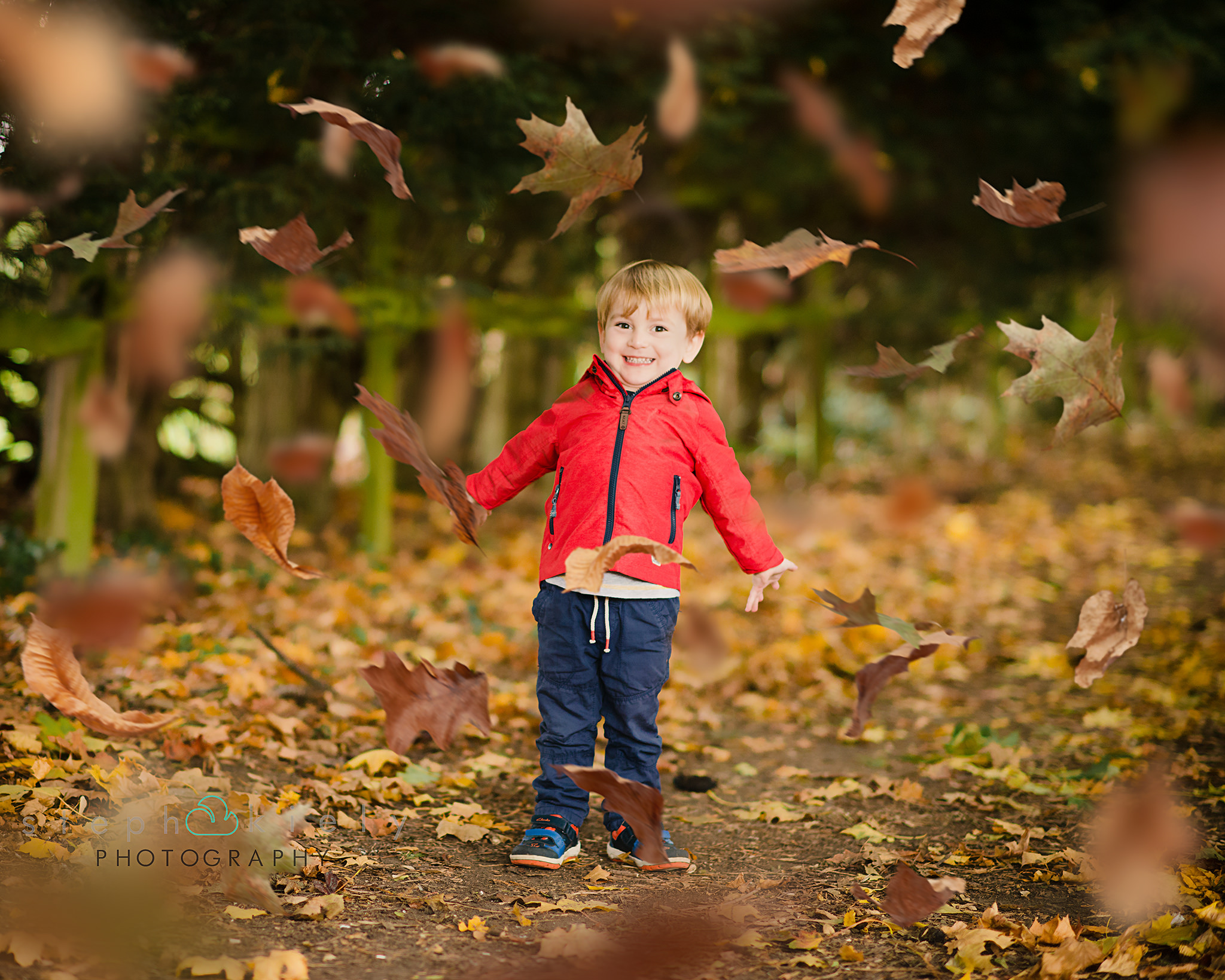 Little boy in a red coat throwing leaves in the air | Children's Photographer Aylesbury Buckinghamshire and Thame Oxfordshire