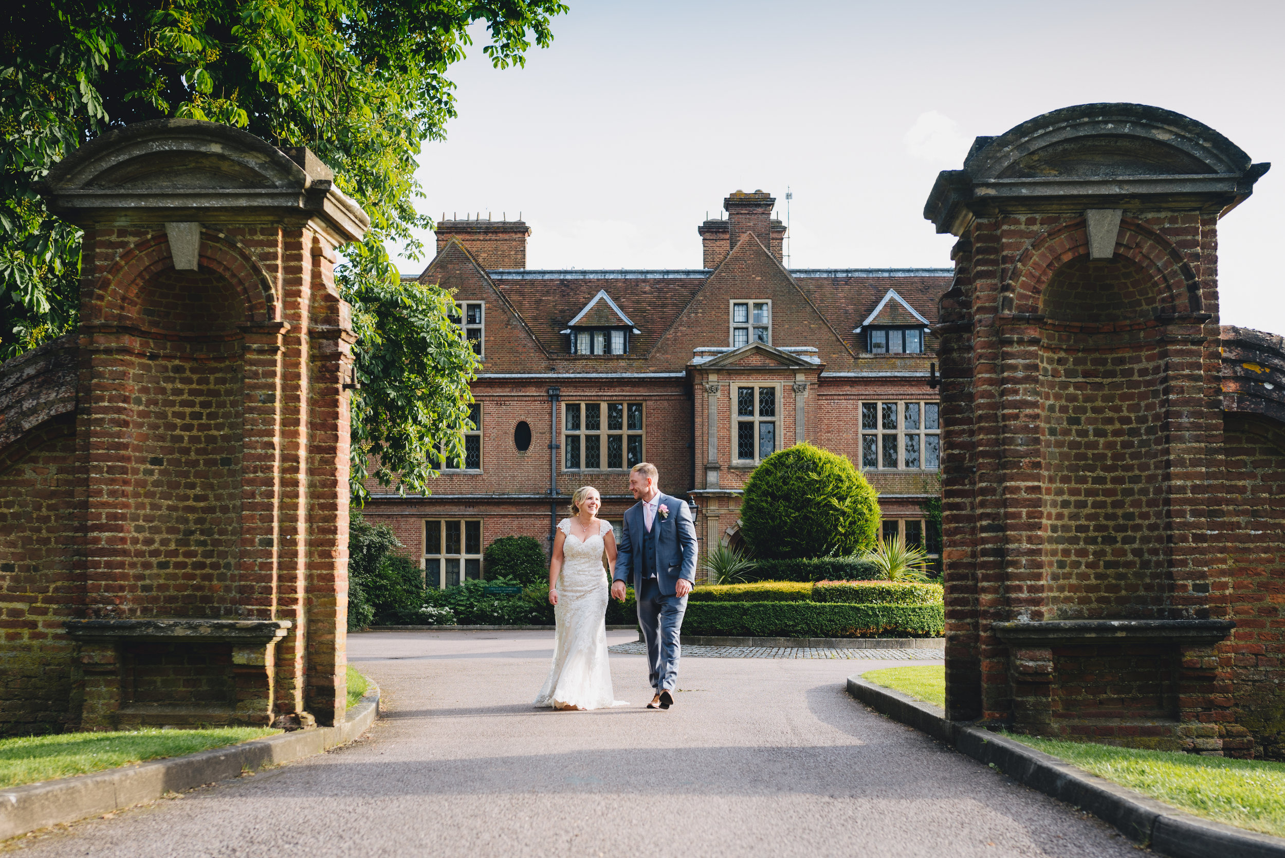 bride and groom walking the driveway of Horwood House, Buckinghamshire