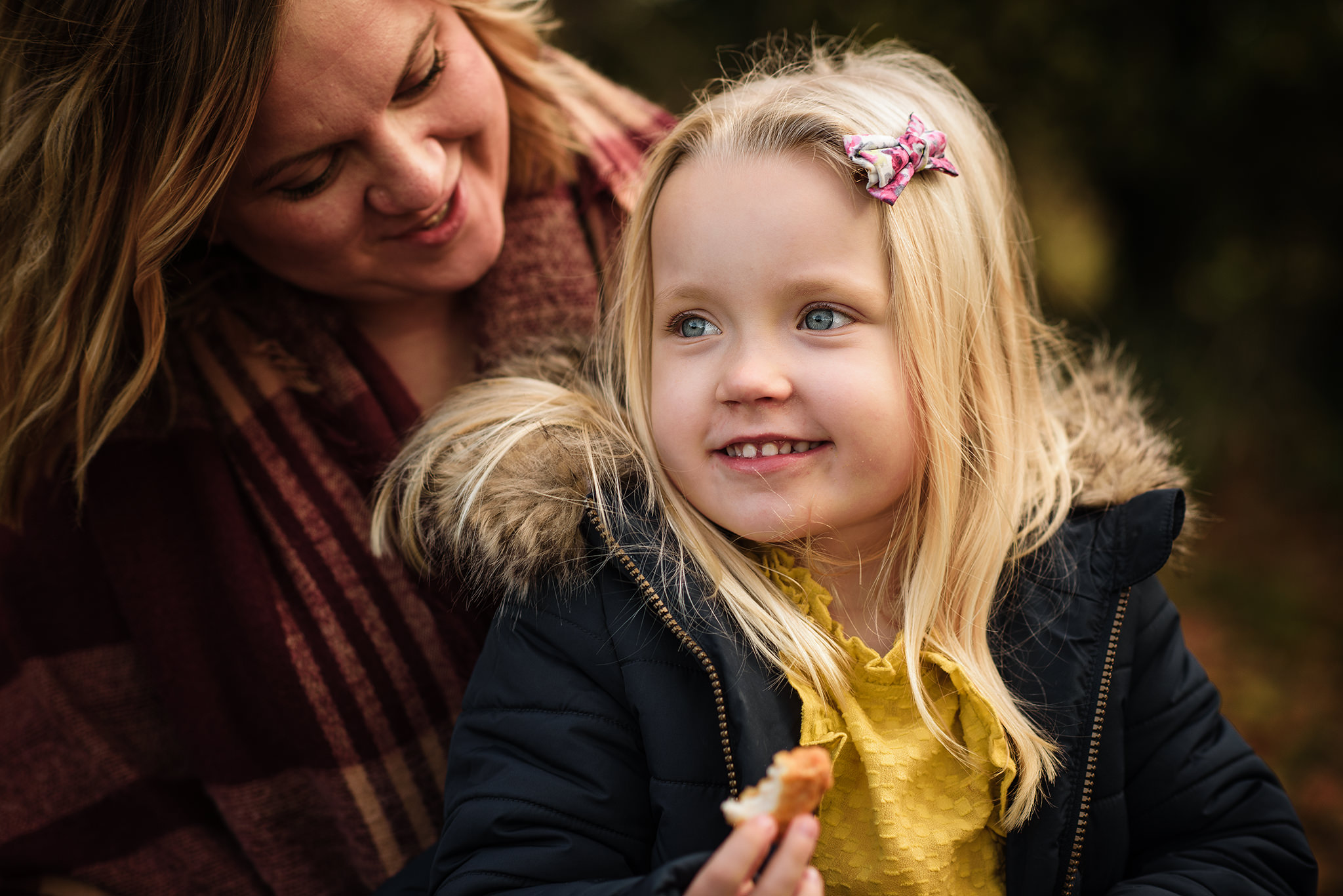 Little girl dressed in yellow and a navy coat sat smiling on her mummies lap during a photo session in aylesbury buckinghamshire and thame oxfordshire