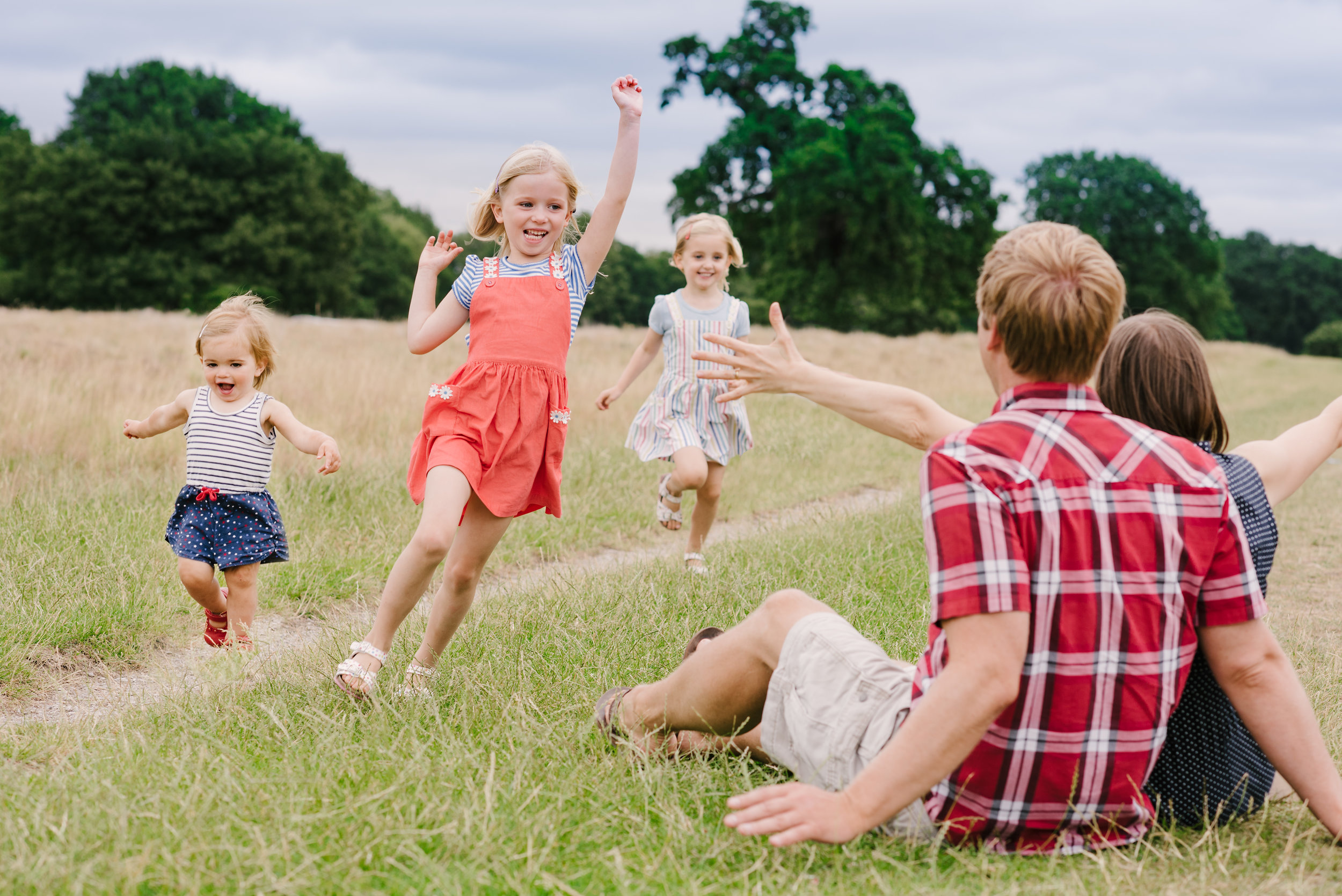 Three little girls running towards their mummy and daddy sat down in the park during a photo session in aylesbury buckinghamshire and thame oxfordshire
