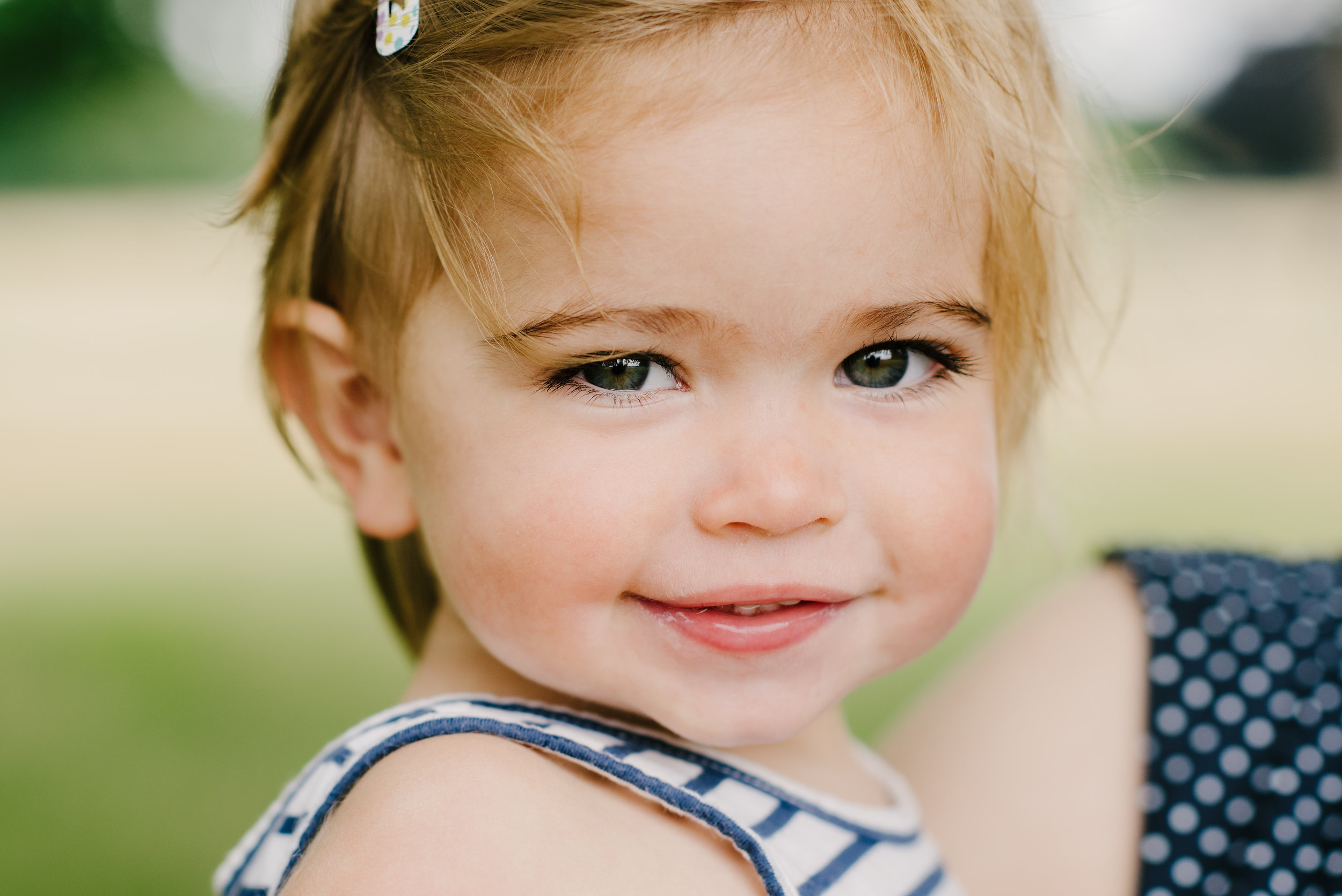 close up of a little girl being held by mummy smiling to camera in the park | Children's Photographer Aylesbury Buckinghamshire and Thame Oxfordshire