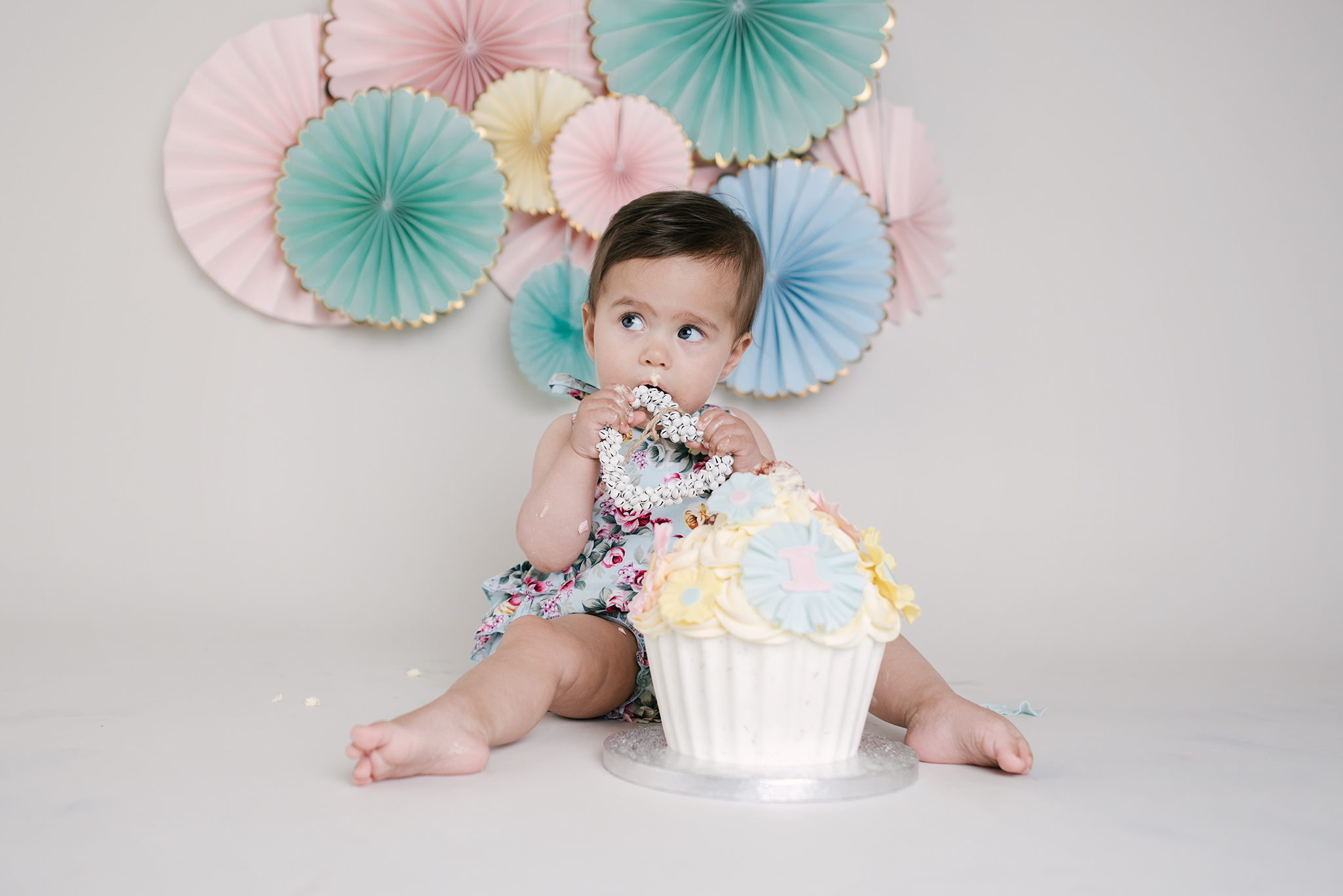 Little girl wearing mint and pink floral romper with fans behind eating cake | Cake Smash Photographer Aylesbury Buckinghamshire and Thame Oxfordshire