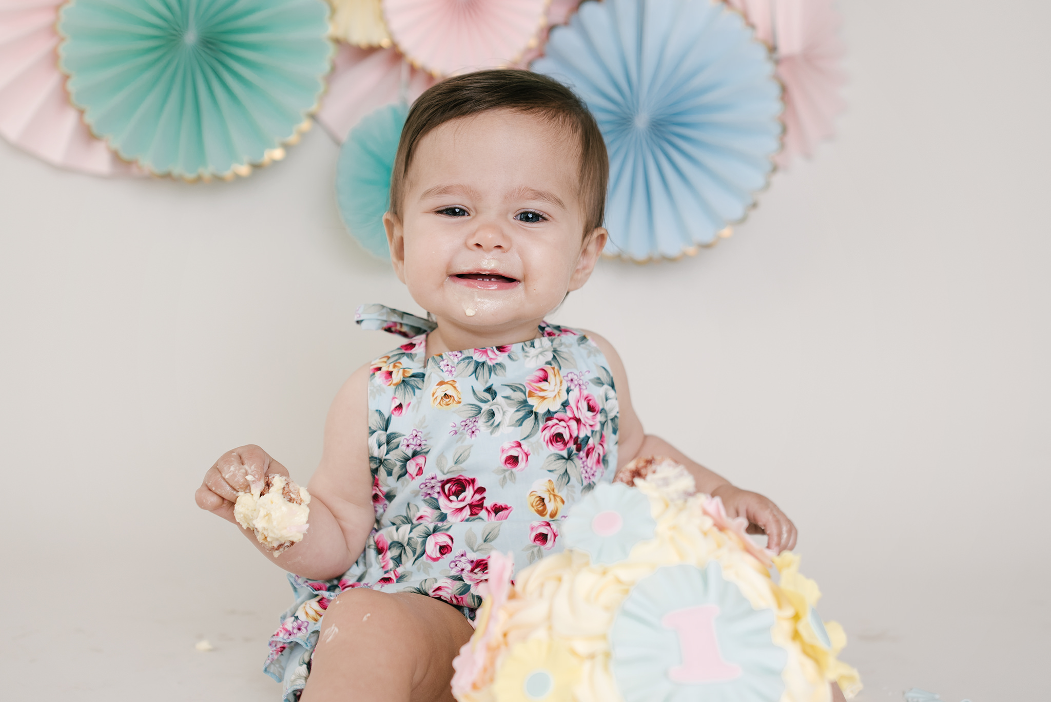 little girl wearing mint and floral romper smiling as she eats cake | Cake Smash Photographer Aylesbury Buckinghamshire and Thame Oxfordshire