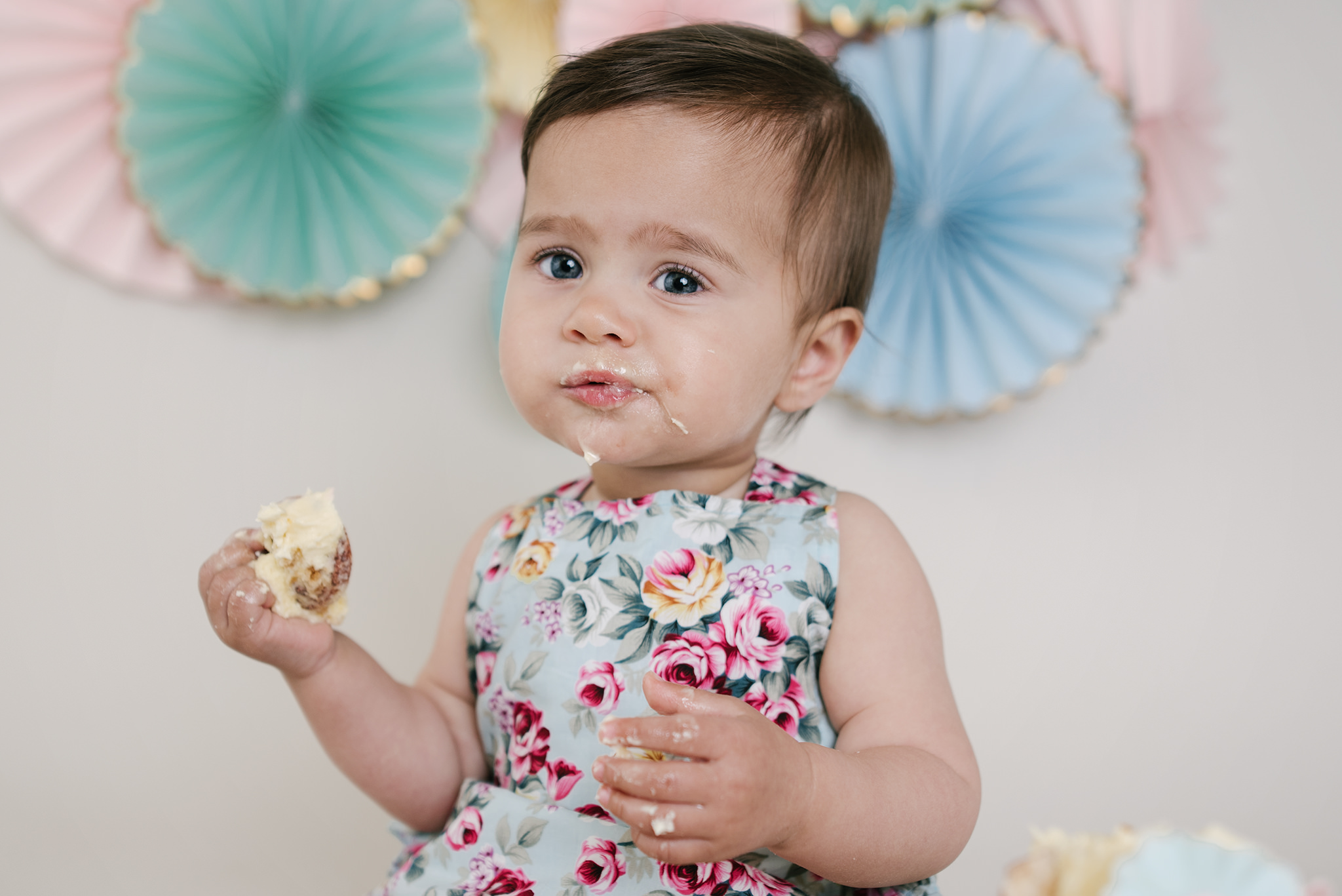 little girl with fans behind with a mouthful of cake | Cake Smash Photographer Aylesbury Buckinghamshire and Thame Oxfordshire