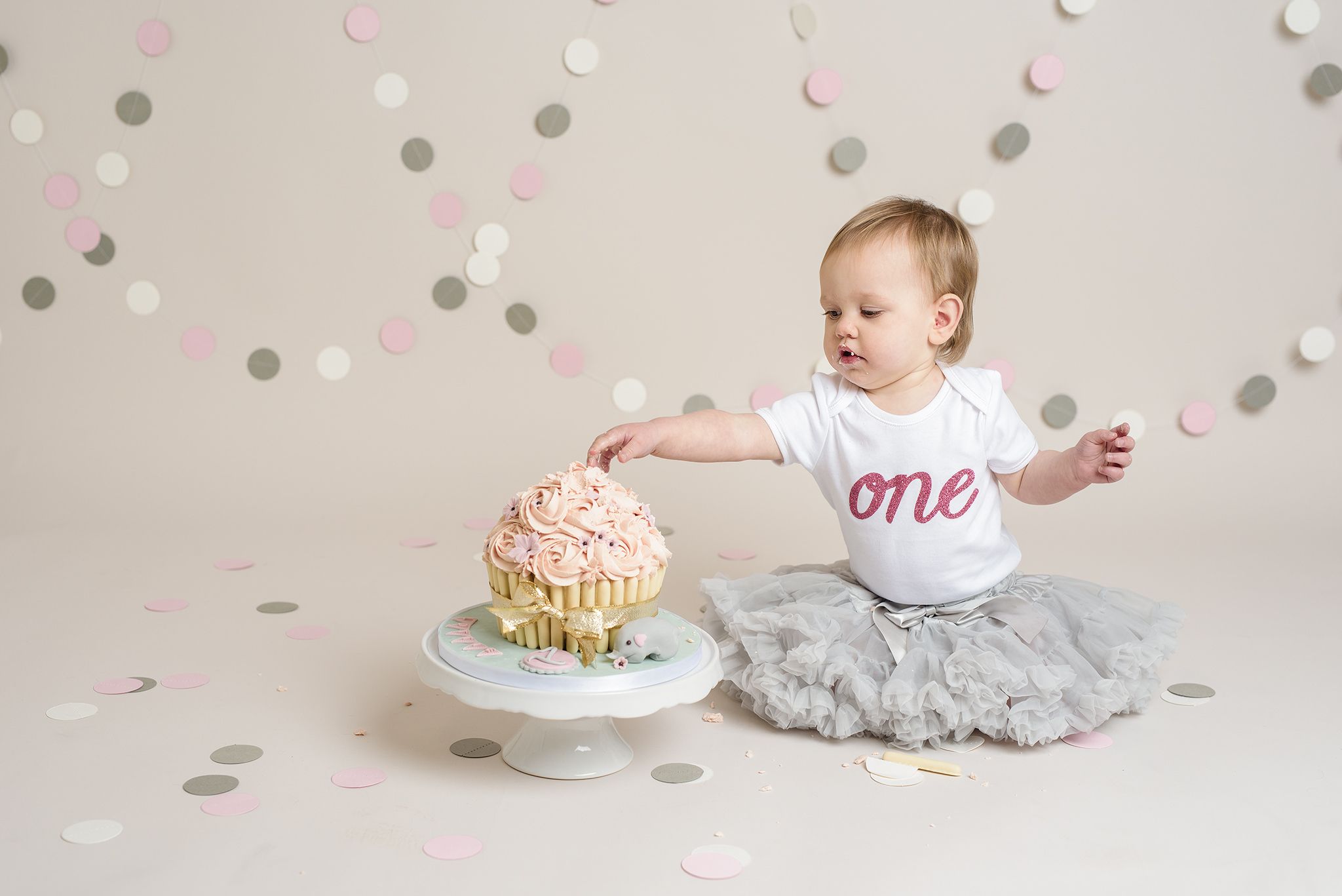 Little girl in grey tutu reaching for her cake | Cake Smash Photographer Aylesbury Buckinghamshire and Thame Oxfordshire