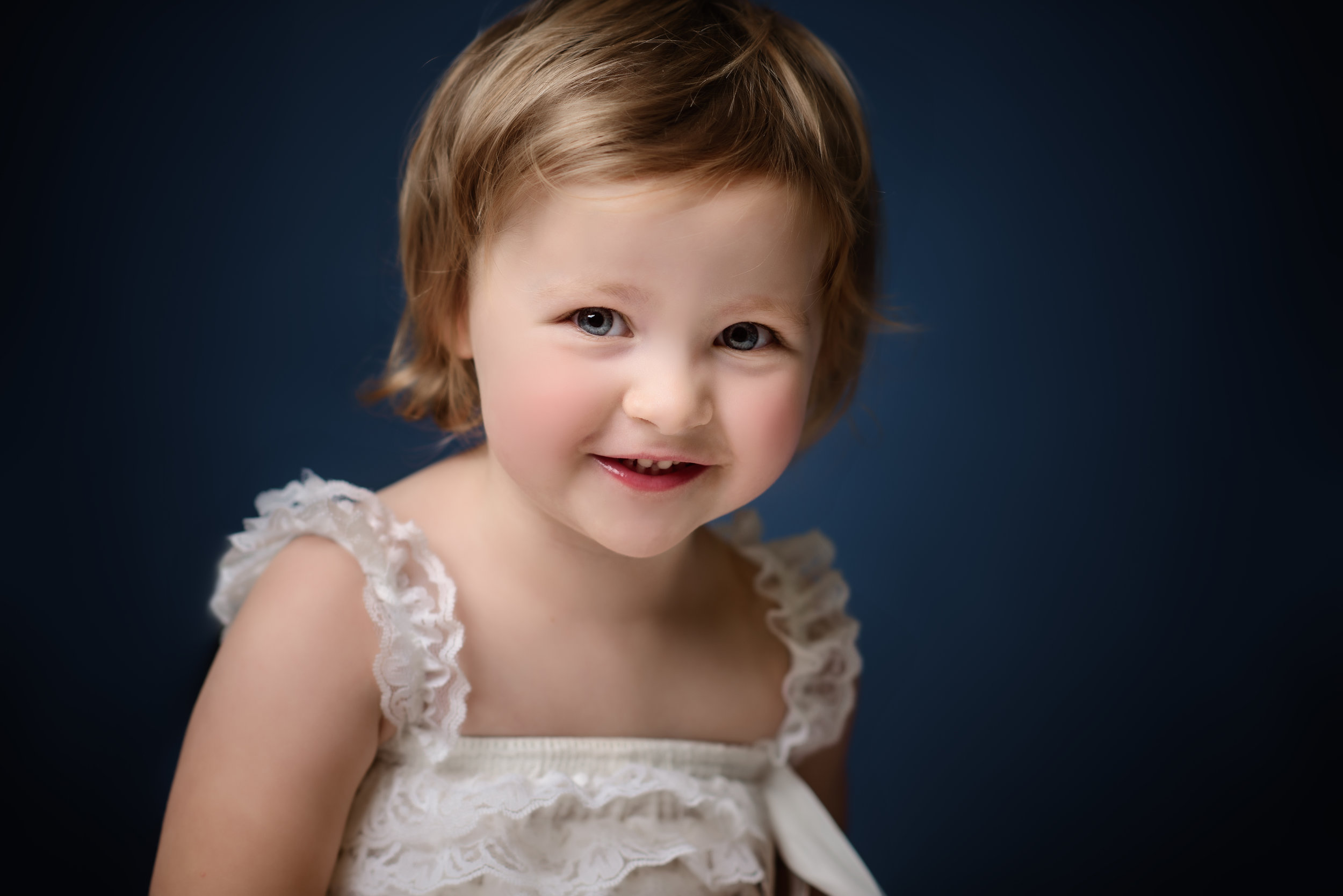Little girl with dark blue background smiling in to camera | Children's Photographer Aylesbury Buckinghamshire and Thame Oxfordshire