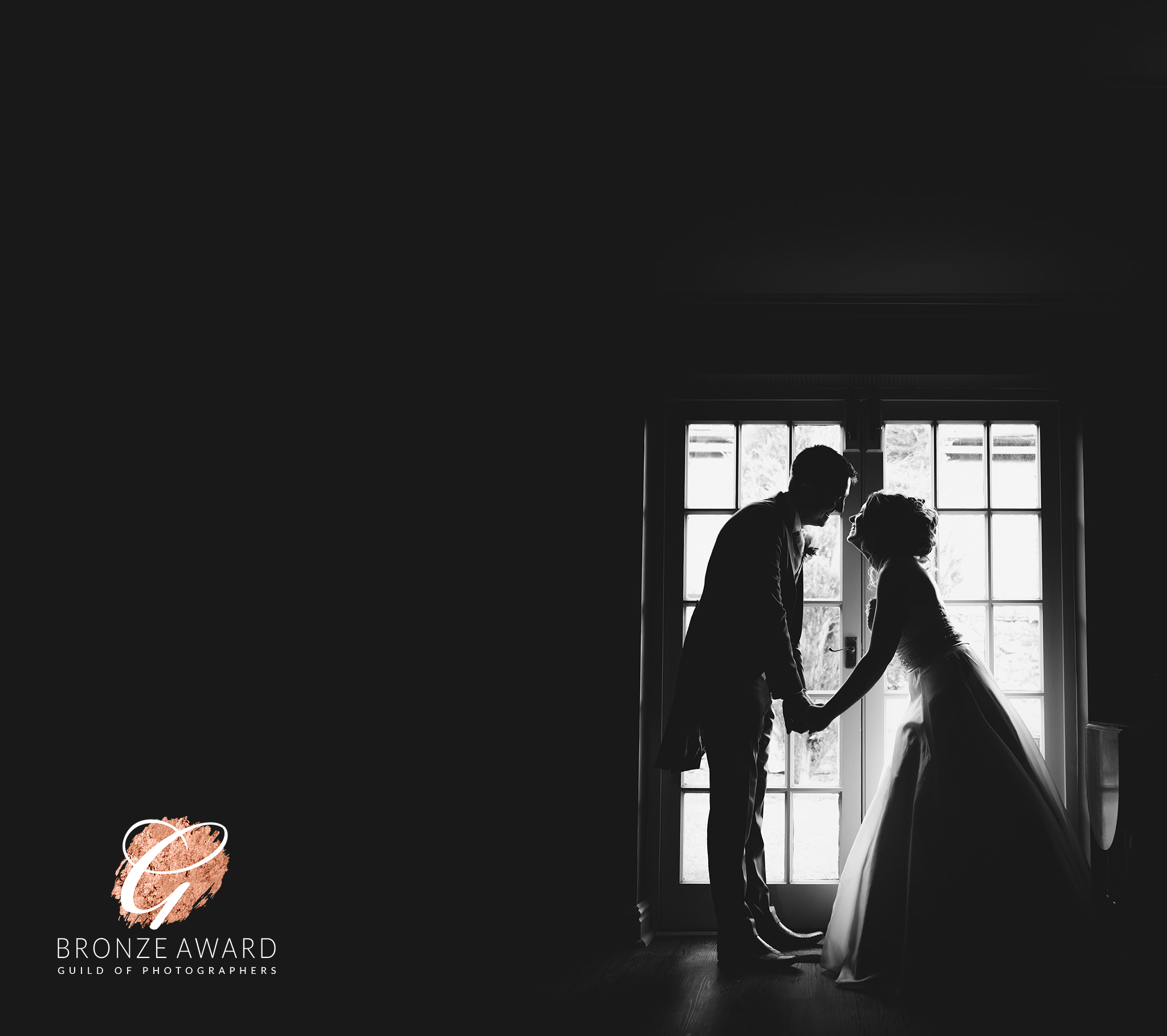 Silhouette in black and white of bride and groom in window at a wedding at The Spread Eagle Thame, Oxfordshire