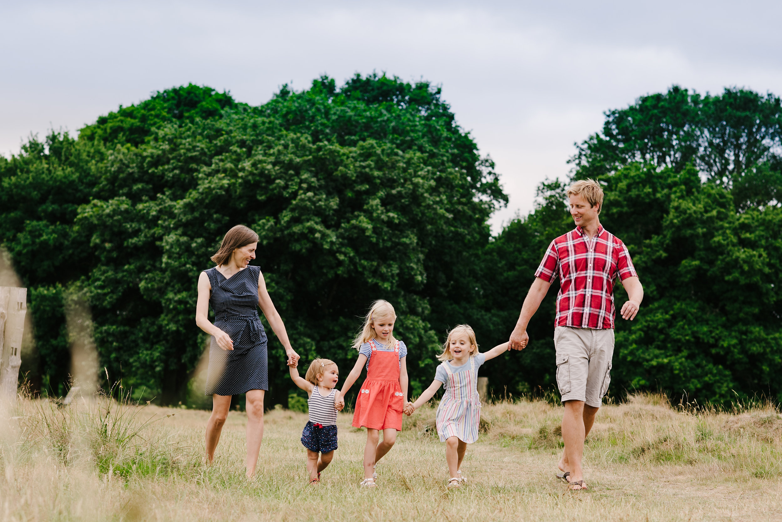 Family of five walking in a line holding hands in the park during a photo session in aylesbury buckinghamshire and thame oxfordshire
