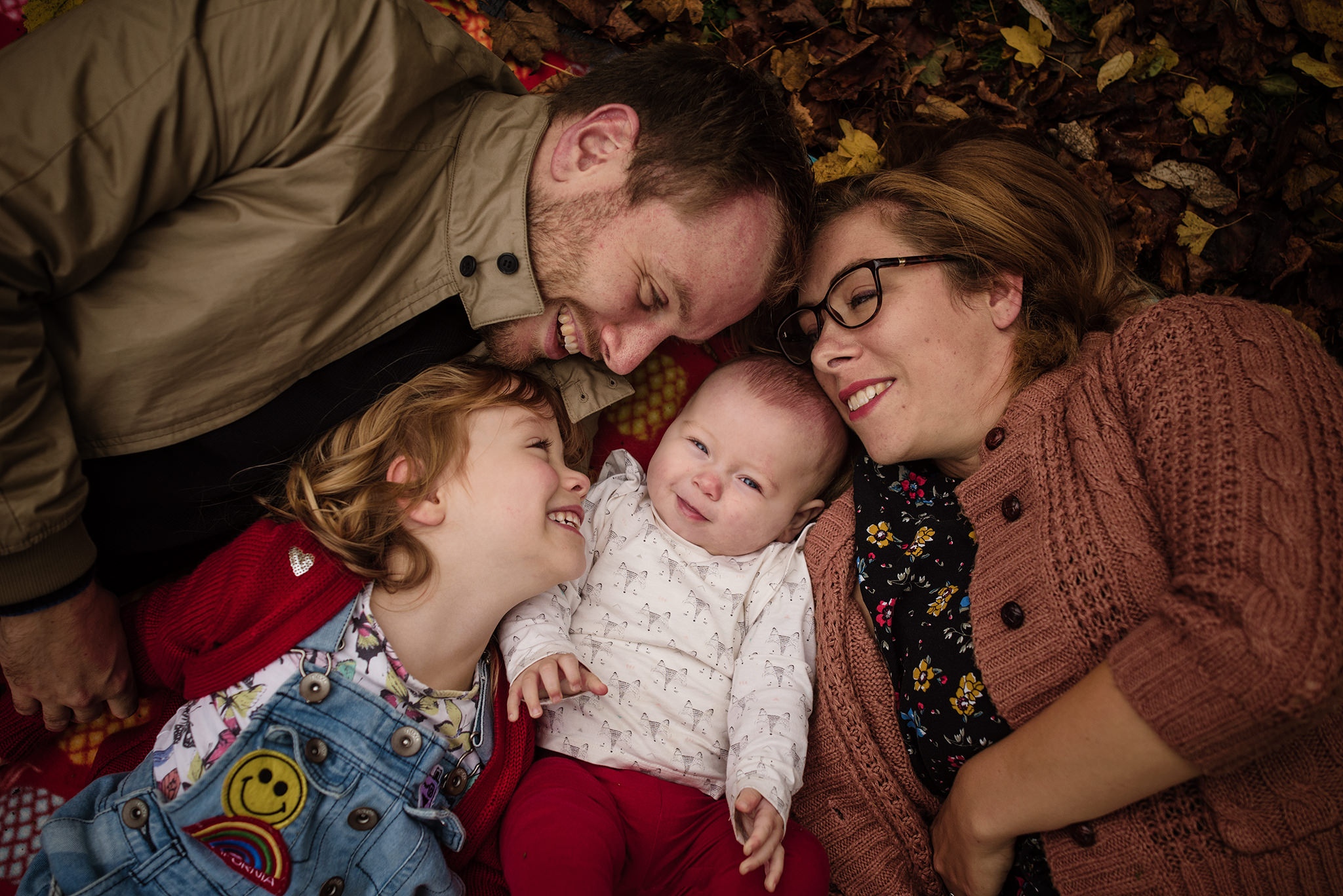Family of five cuddling up in the leaves during a photo session in aylesbury buckinghamshire and thame oxfordshire