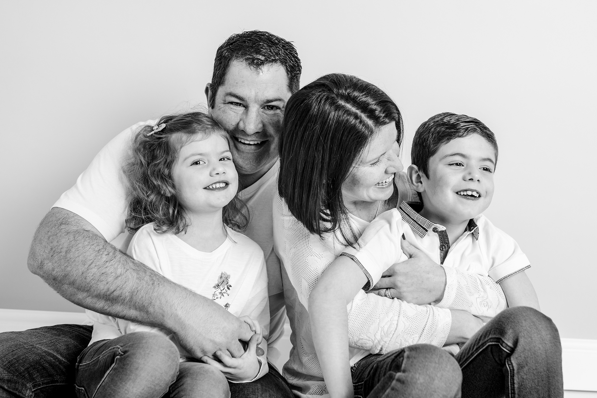 Family of four having a tickle fight in the studio during a photo session in aylesbury buckinghamshire and thame oxfordshire