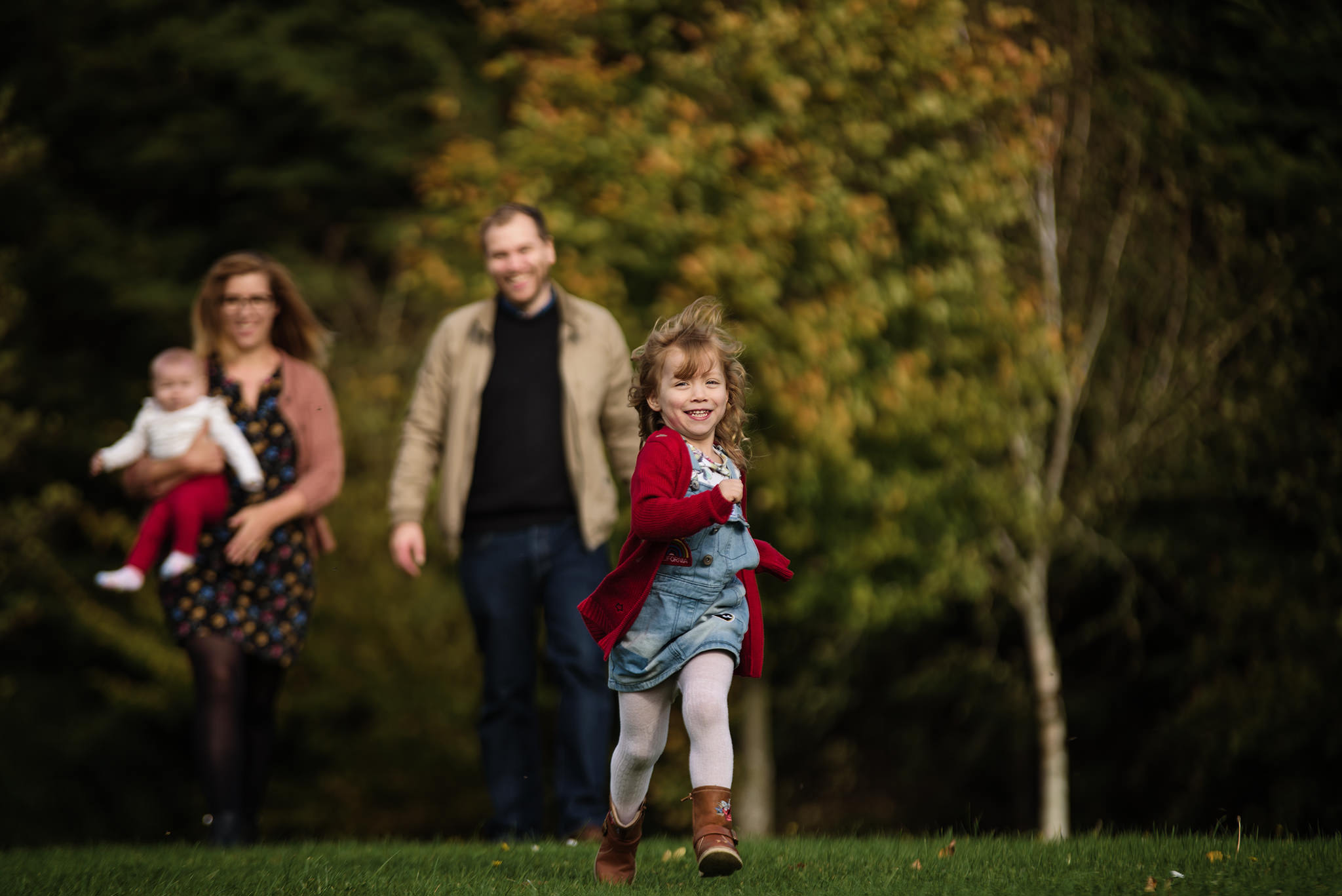 Family of four walking towards camera in the park, little girl running towards ahead of her parents during a photo session in aylesbury buckinghamshire and thame oxfordshire