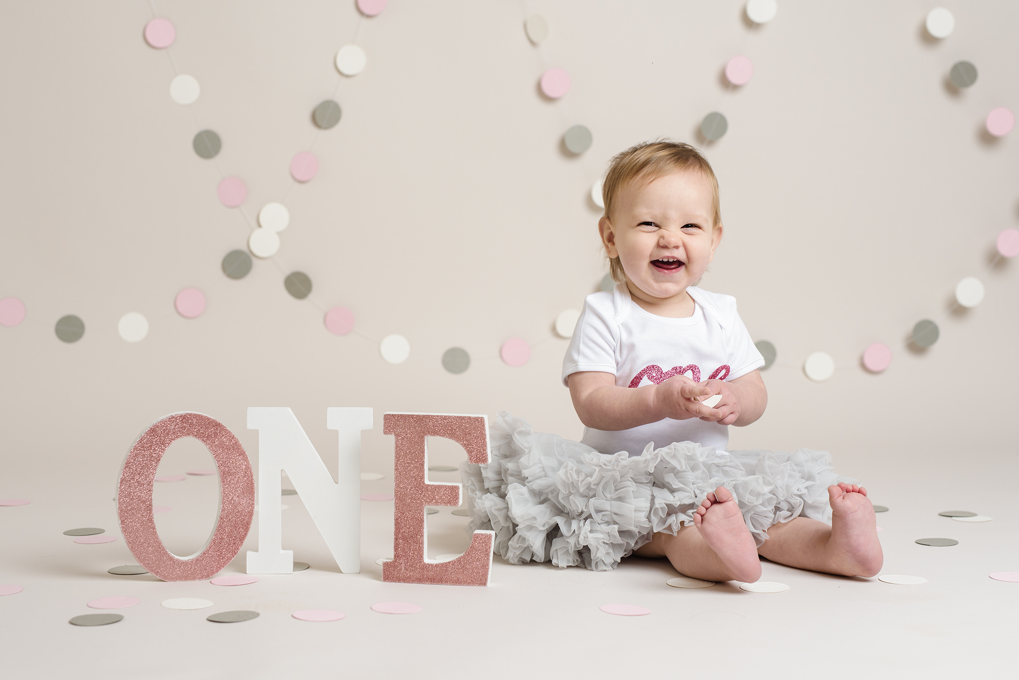 little girl laughing next to a one sign | Cake Smash Photographer Aylesbury Buckinghamshire and Thame Oxfordshire