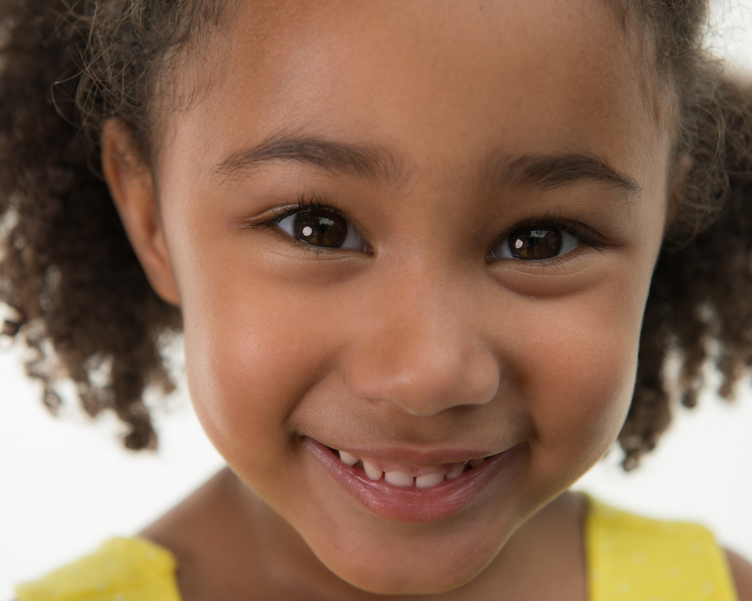 Close up of a little girl wearing yellow smiling in to camera | Children's Photographer Aylesbury Buckinghamshire and Thame Oxfordshire