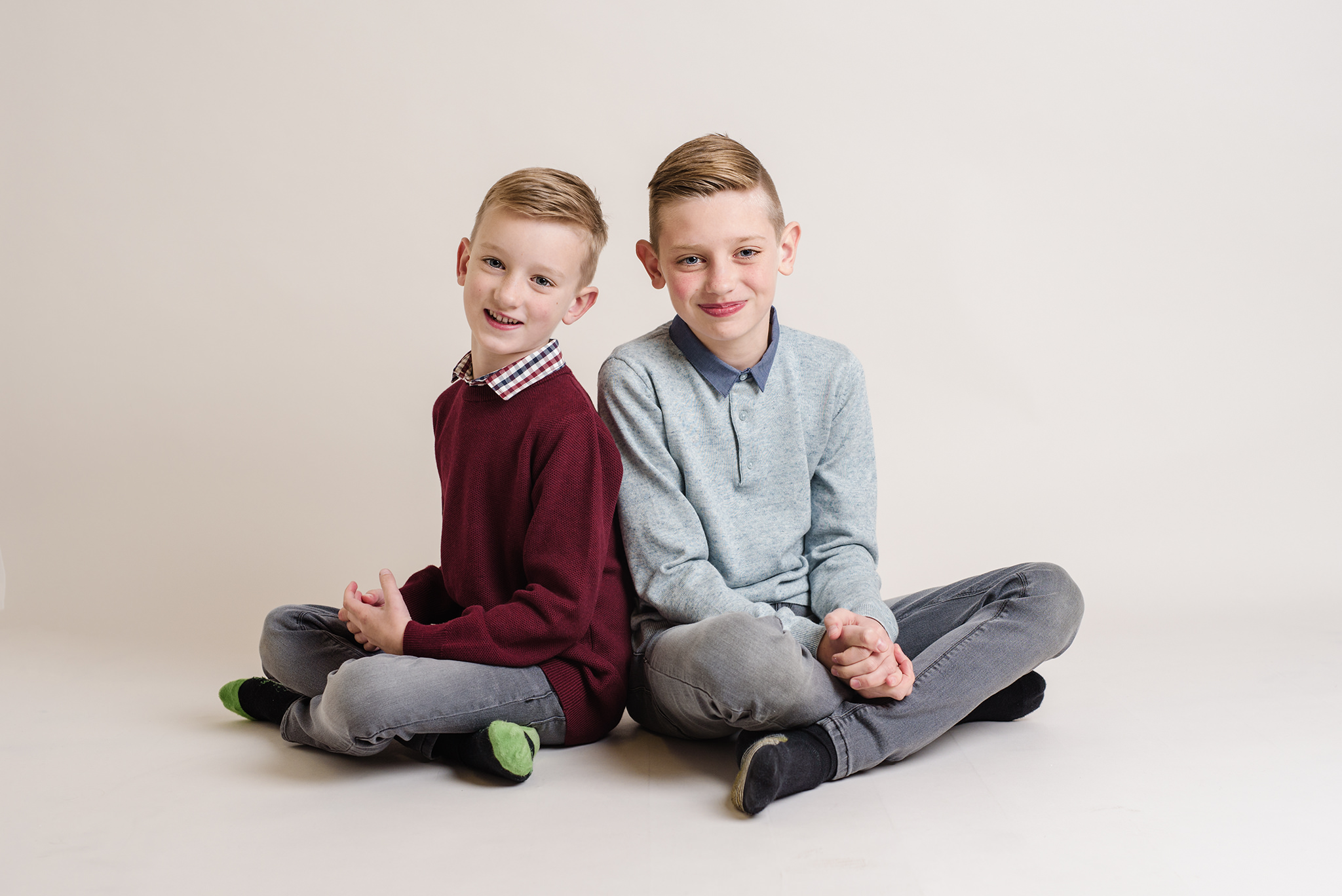 Two brothers sitting back to back cross legged in the studio | Children's Photographer Aylesbury Buckinghamshire and Thame Oxfordshire