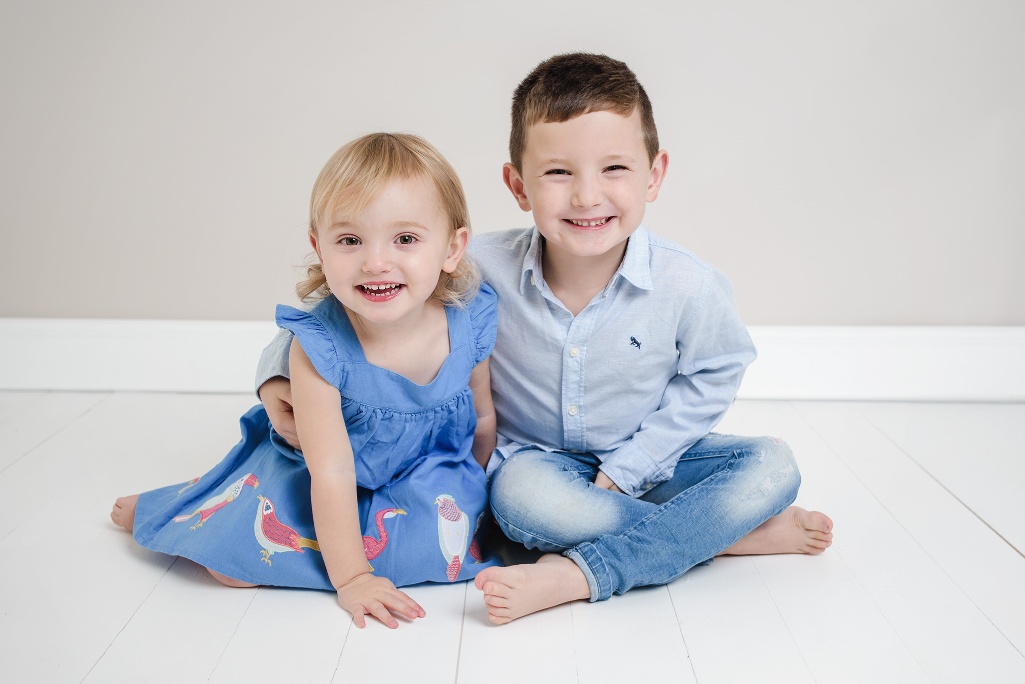 little brother and sister with cheeky smiles to camera | Children's Photographer Aylesbury Buckinghamshire and Thame Oxfordshire