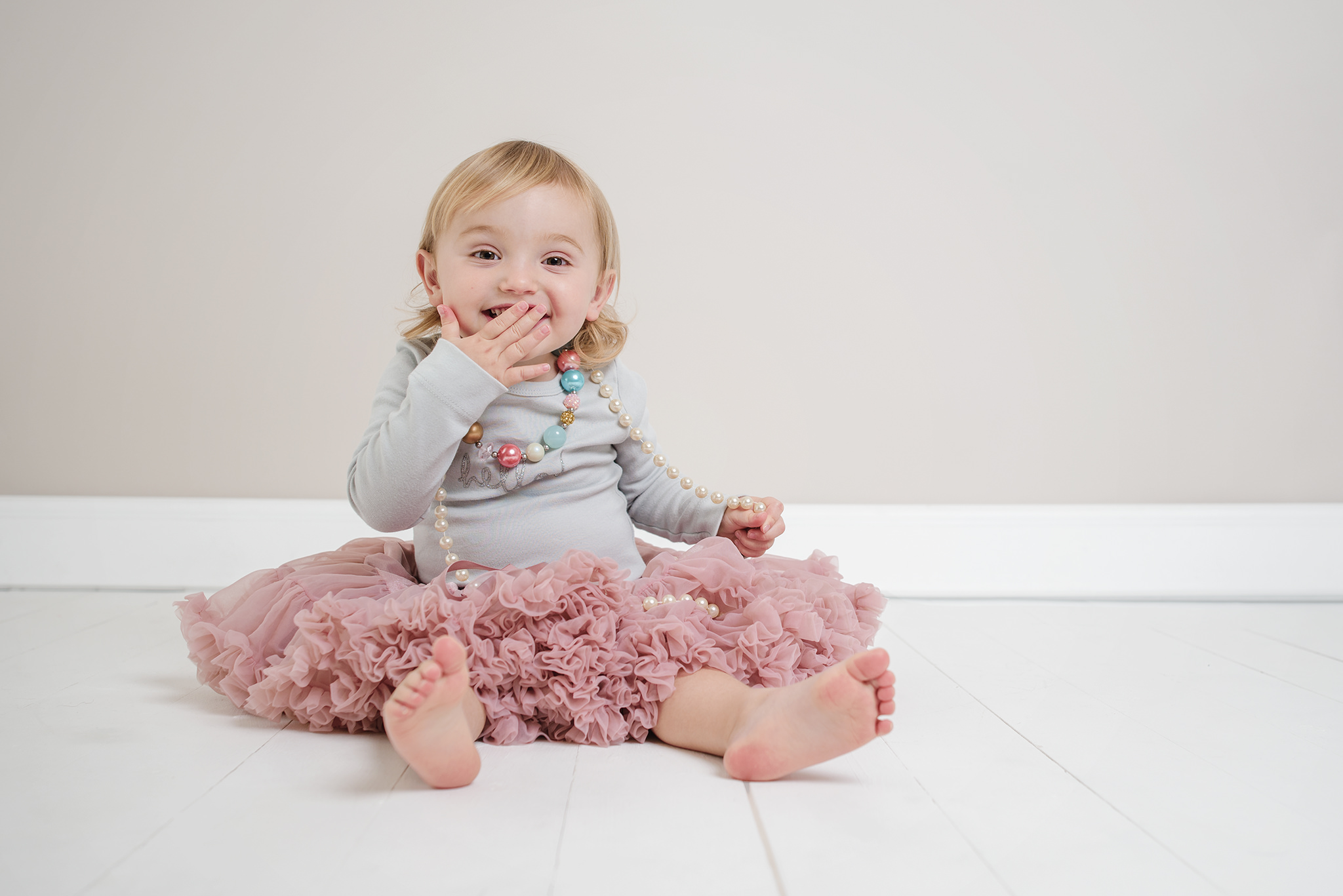 little girl in pink tutu and grey t shirt in the studio. One hand over her mouth with a cheeky smile | Children's Photographer Aylesbury Buckinghamshire and Thame Oxfordshire