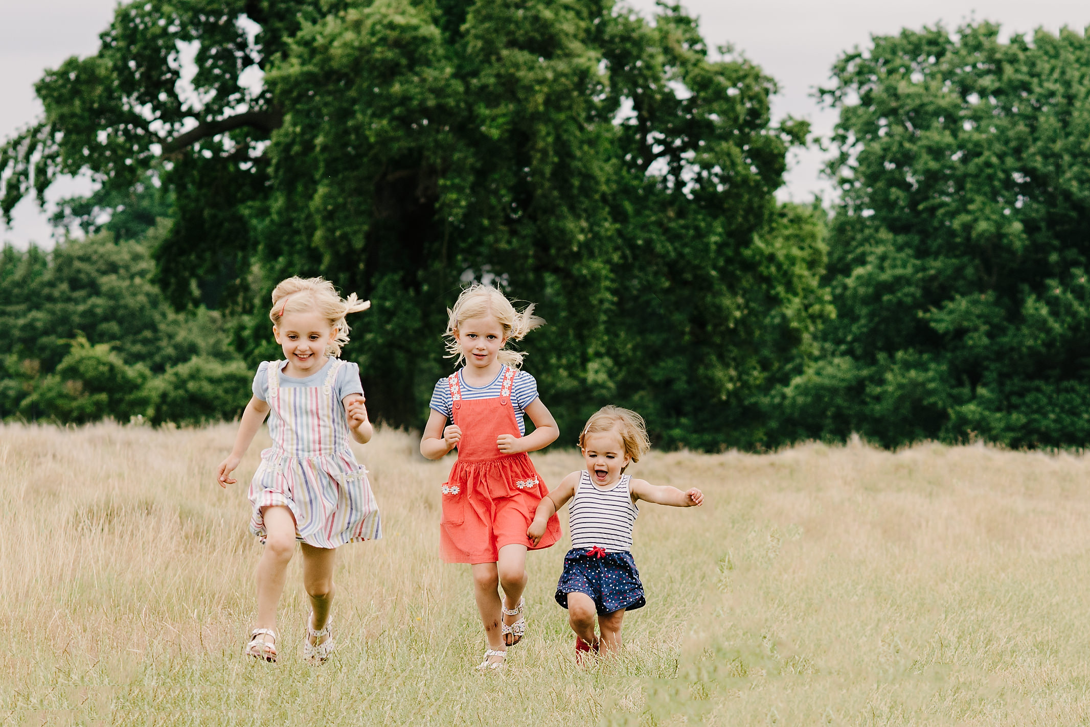 three little girls running towards the camera in the park | Children's Photographer Aylesbury Buckinghamshire and Thame Oxfordshire